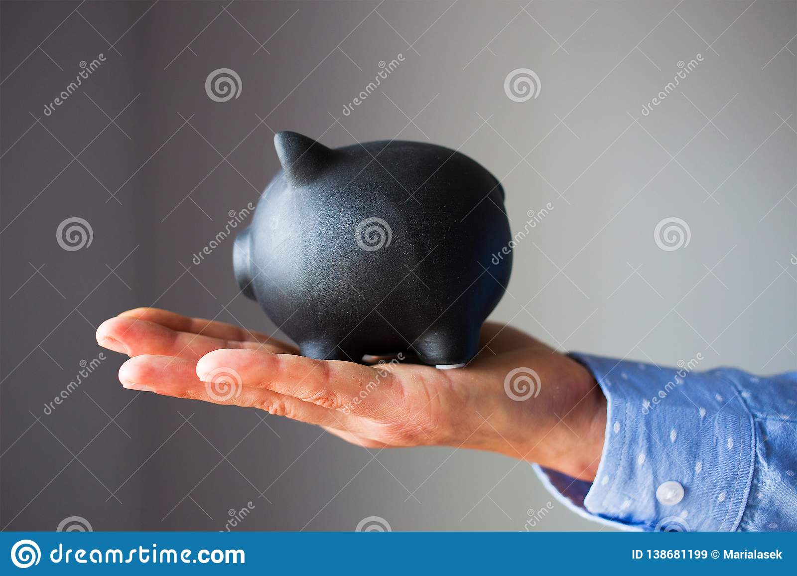 A hand is holding black piggy bank on a white background