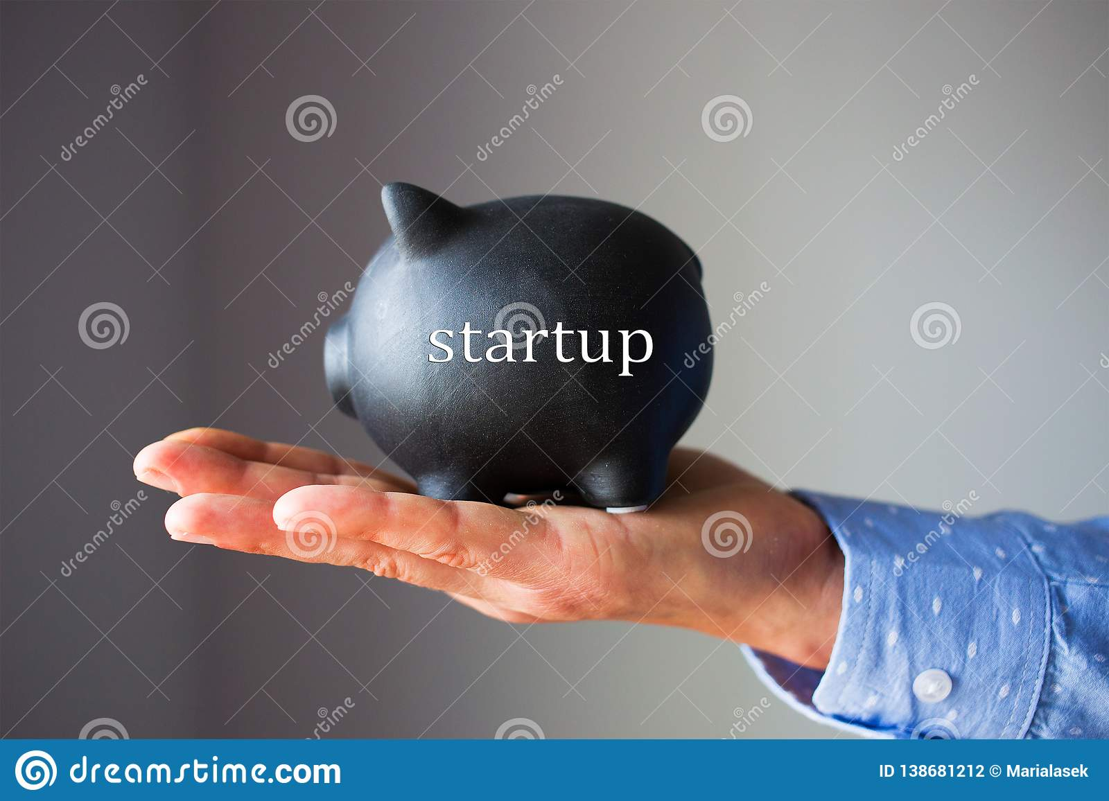 A hand is holding black piggy bank with word startup written on it