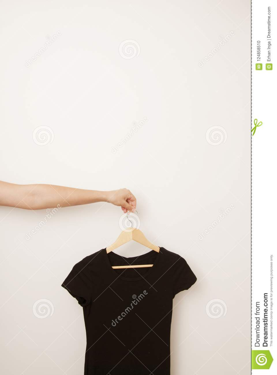 Hand holding black woman dress on wooden clothes hanger on white door with copy space. Isolated. Fashion and daily clothes.