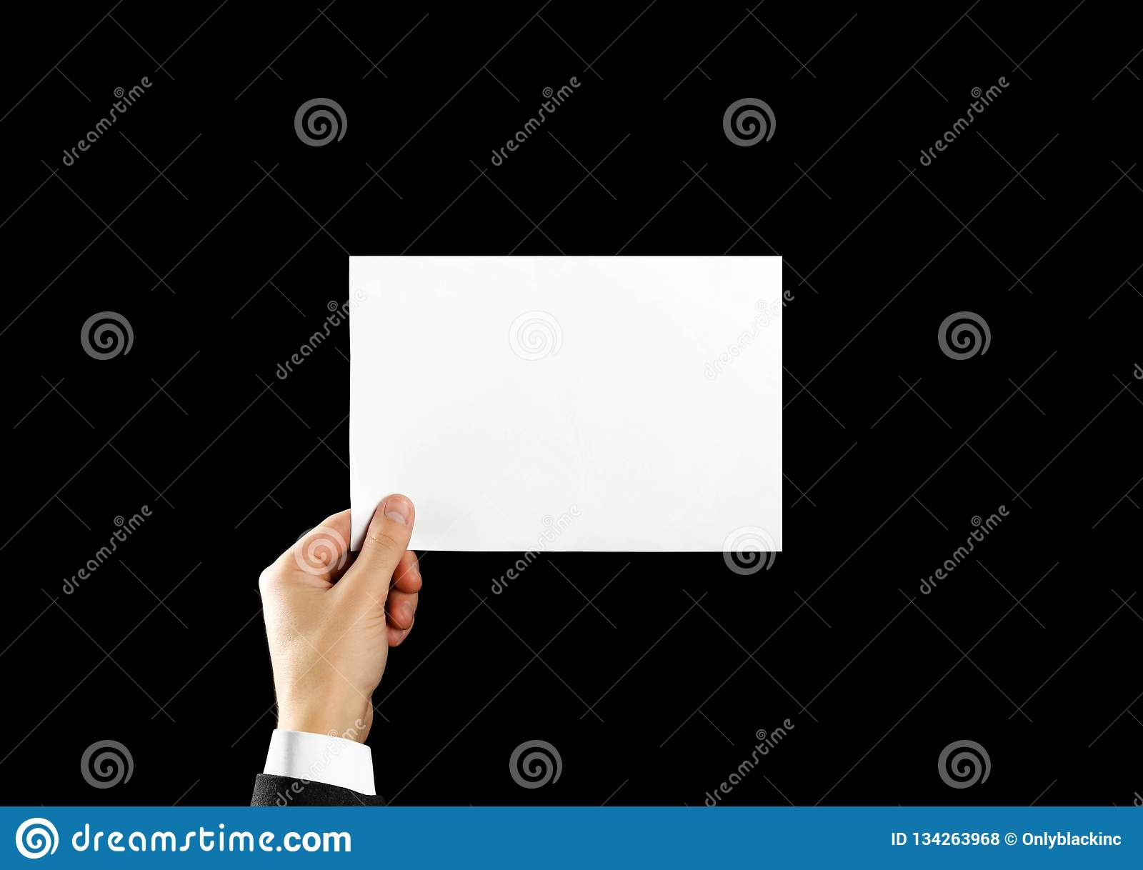 Hand holding blank brochure booklet in the hand. Isolated on black background. Man show offset paper. Sheet template. Book in