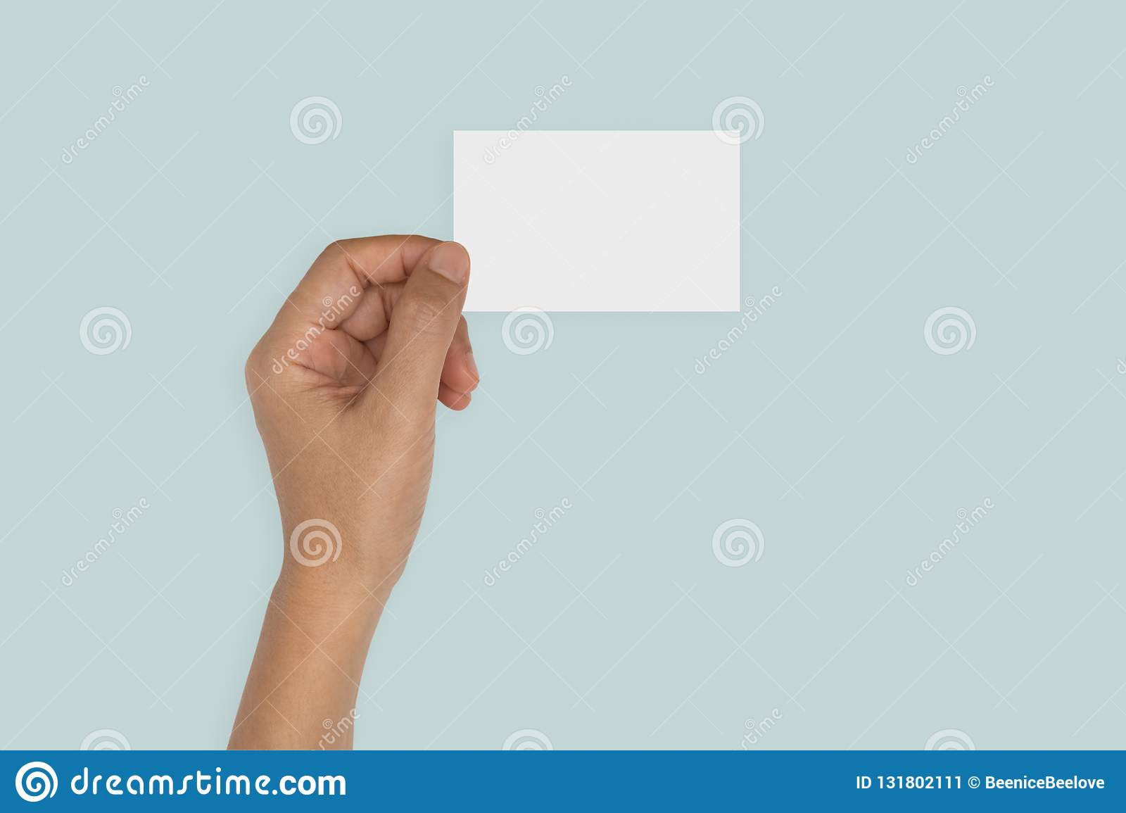 Hand holding blank card isolated on blue