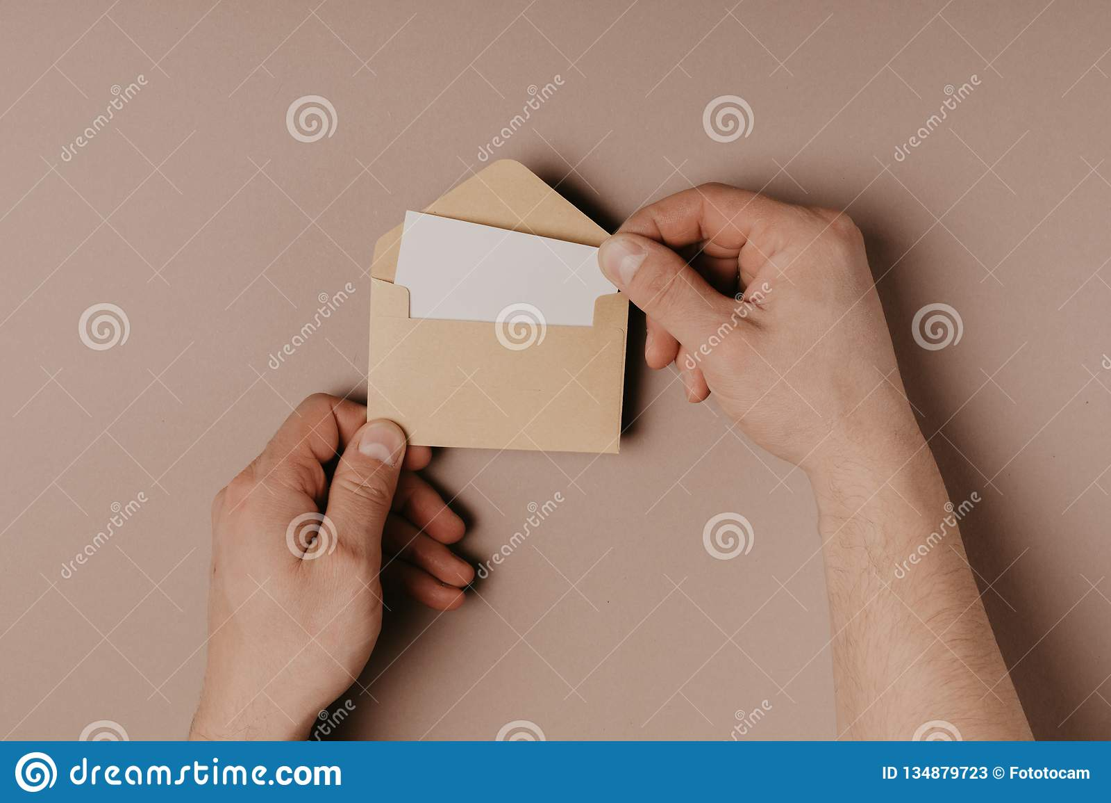 Hand holding blank envelope and letter mockup