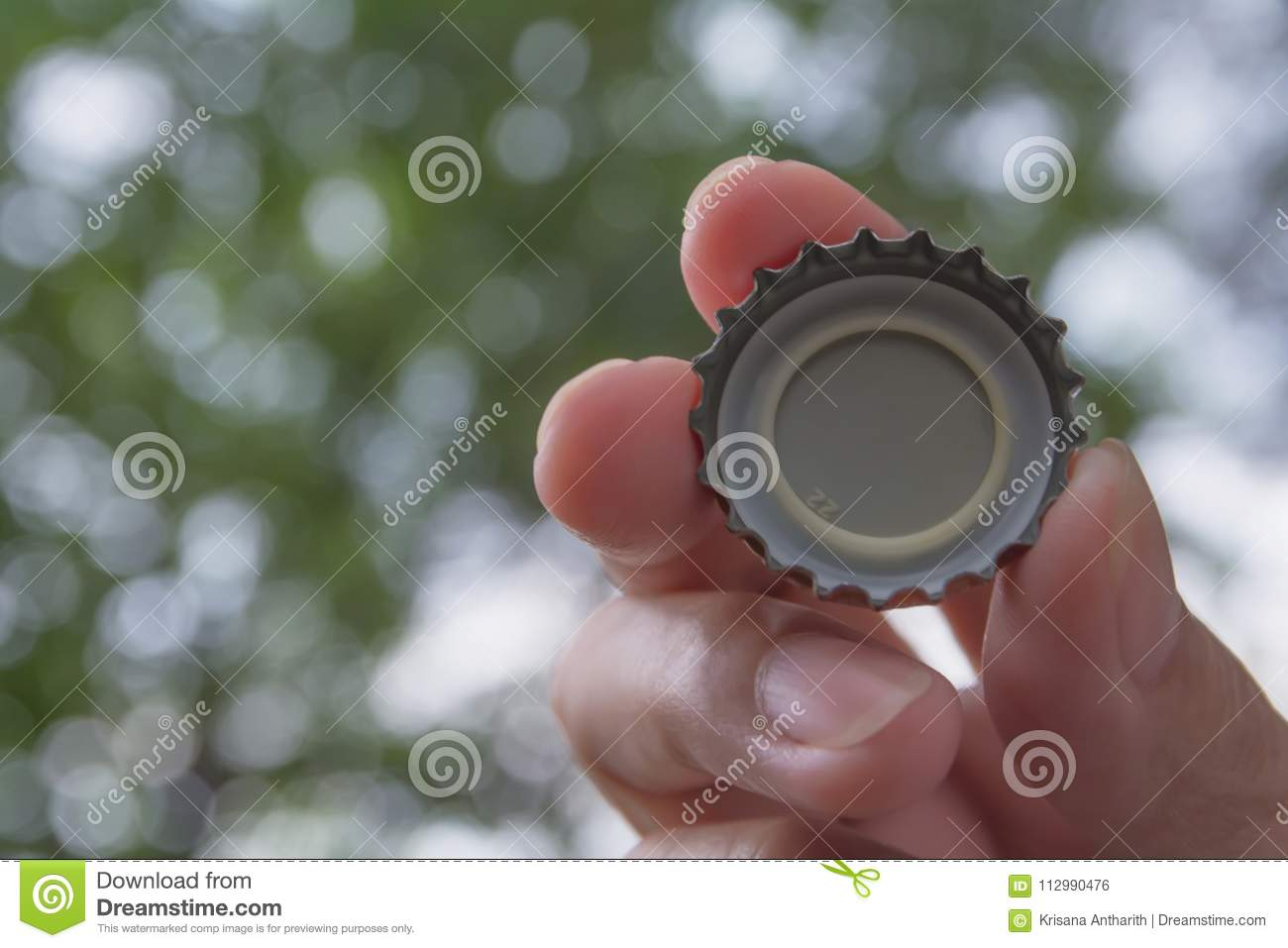 Hand holding a bottle caps on nature background