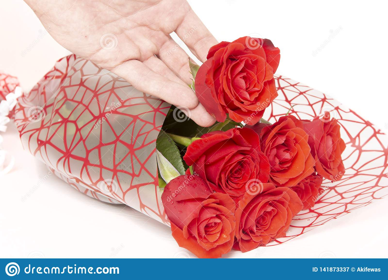 Hand holding a bouquet of roses on a white background