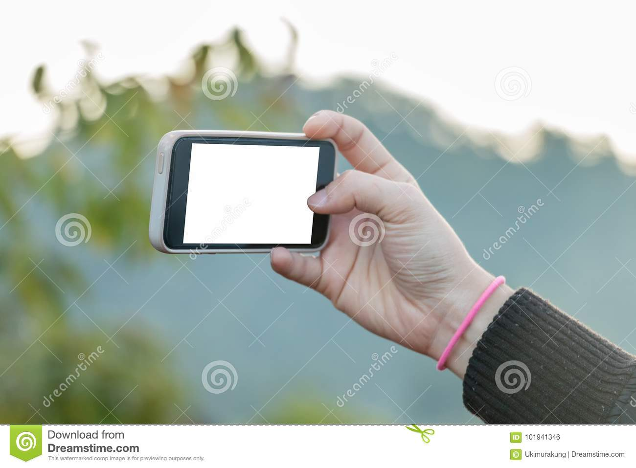 Hand holding cell phone to take a photo, blank screen on white