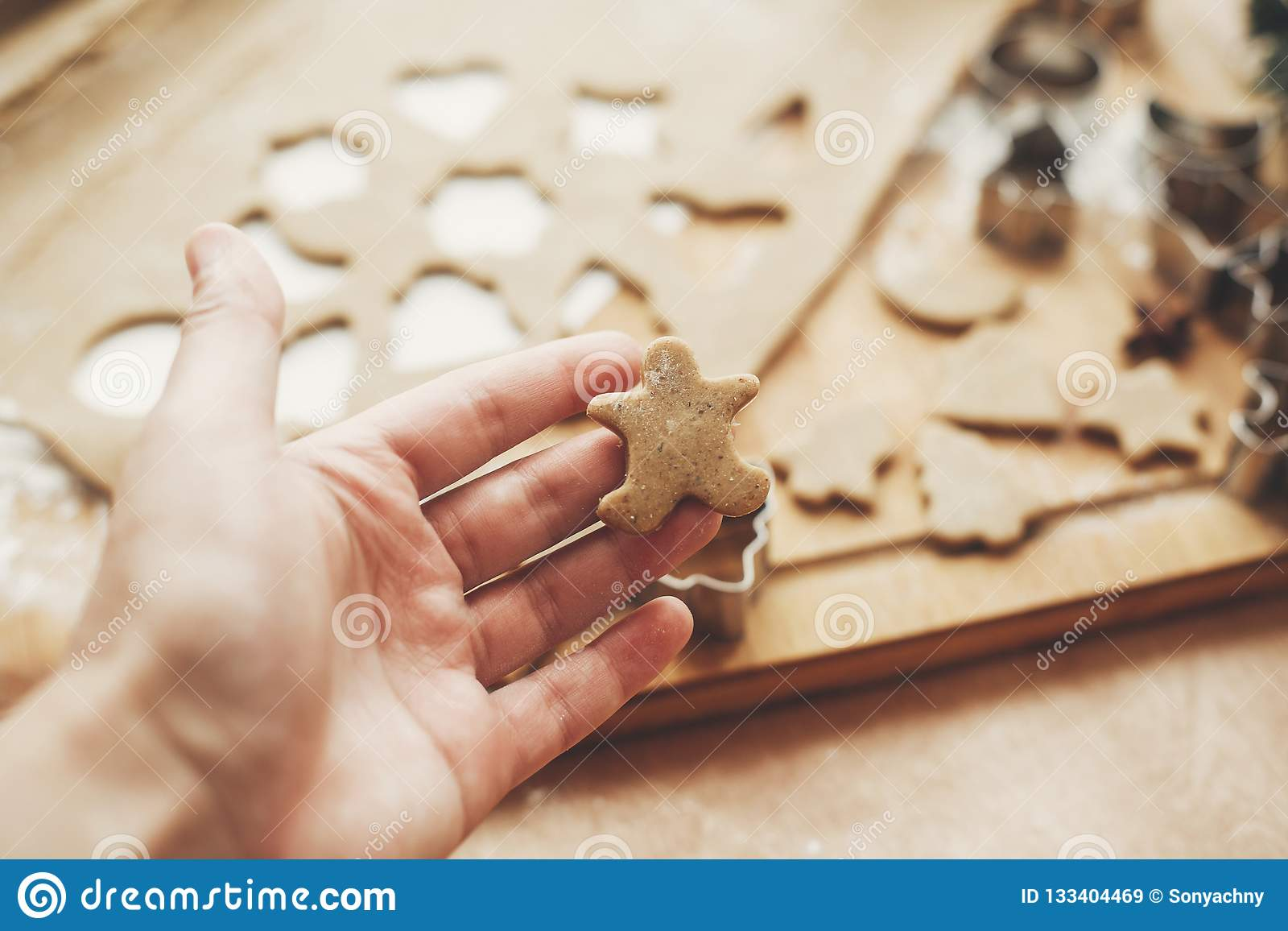 Hand holding christmas gingerbread cookie man on background of w