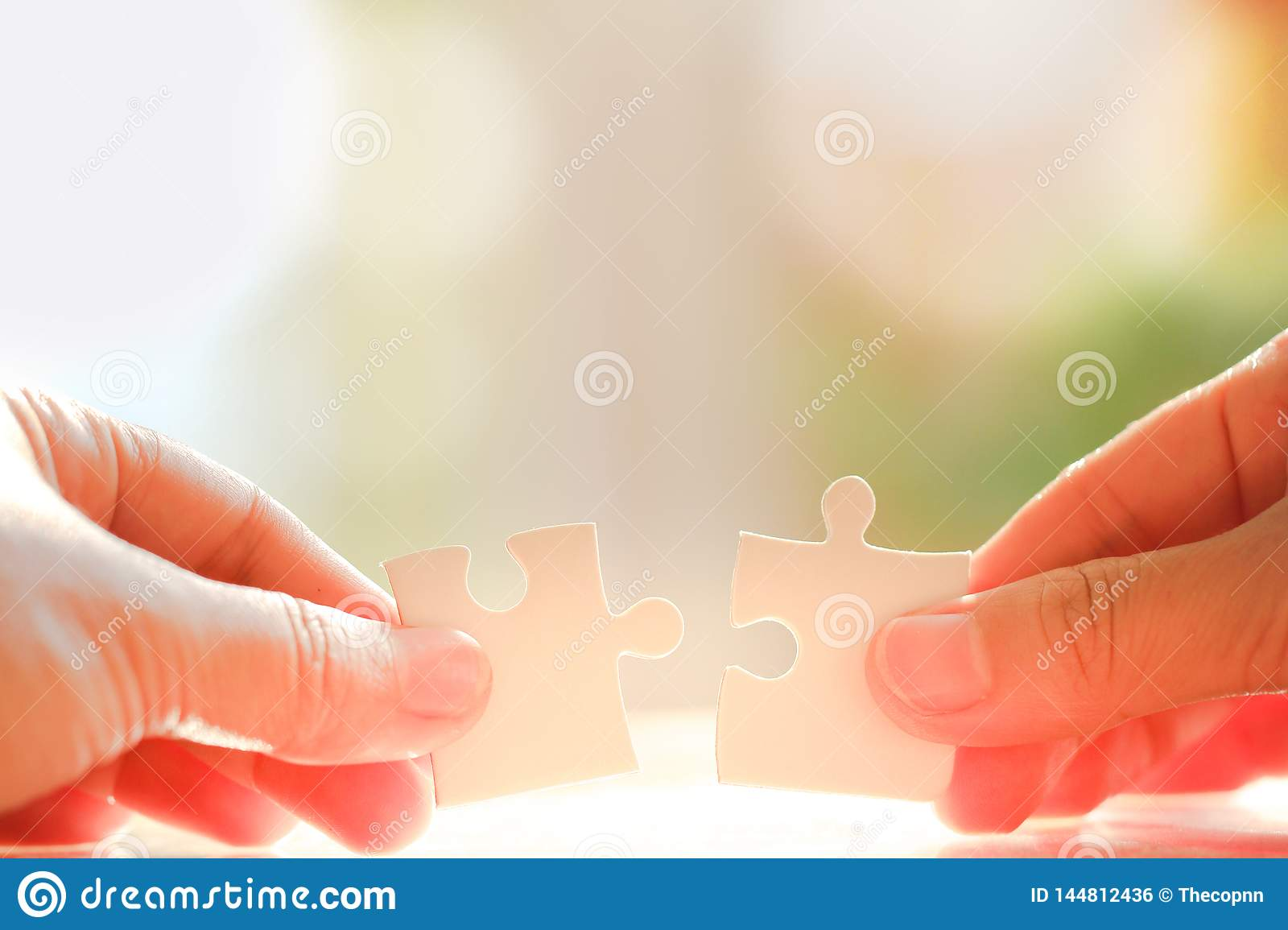 Hand holding and connecting jigsaw puzzles