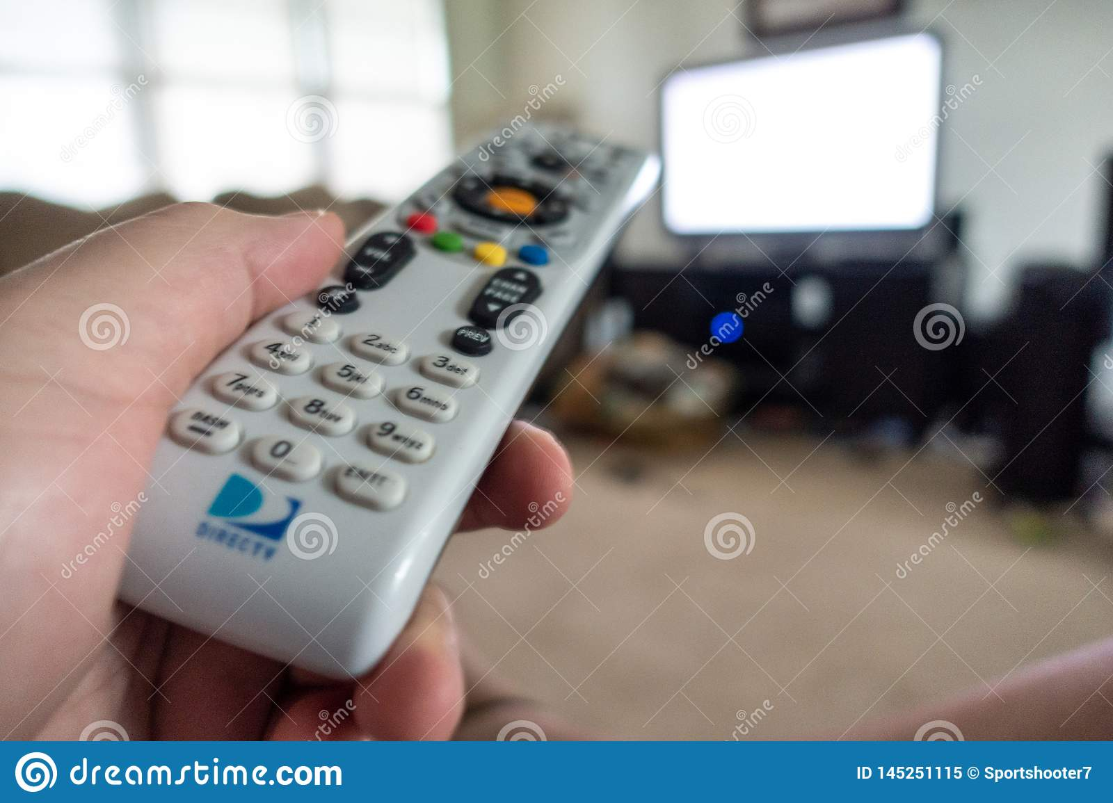 Hand holding DirecTv remote pointing at TV