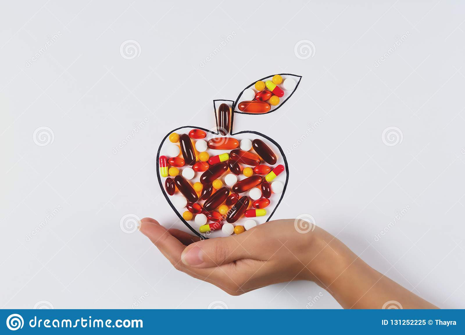 Hand holding drawing apple with colorful capsules and pills on white background. Health care vitamins or synthetic food concept.