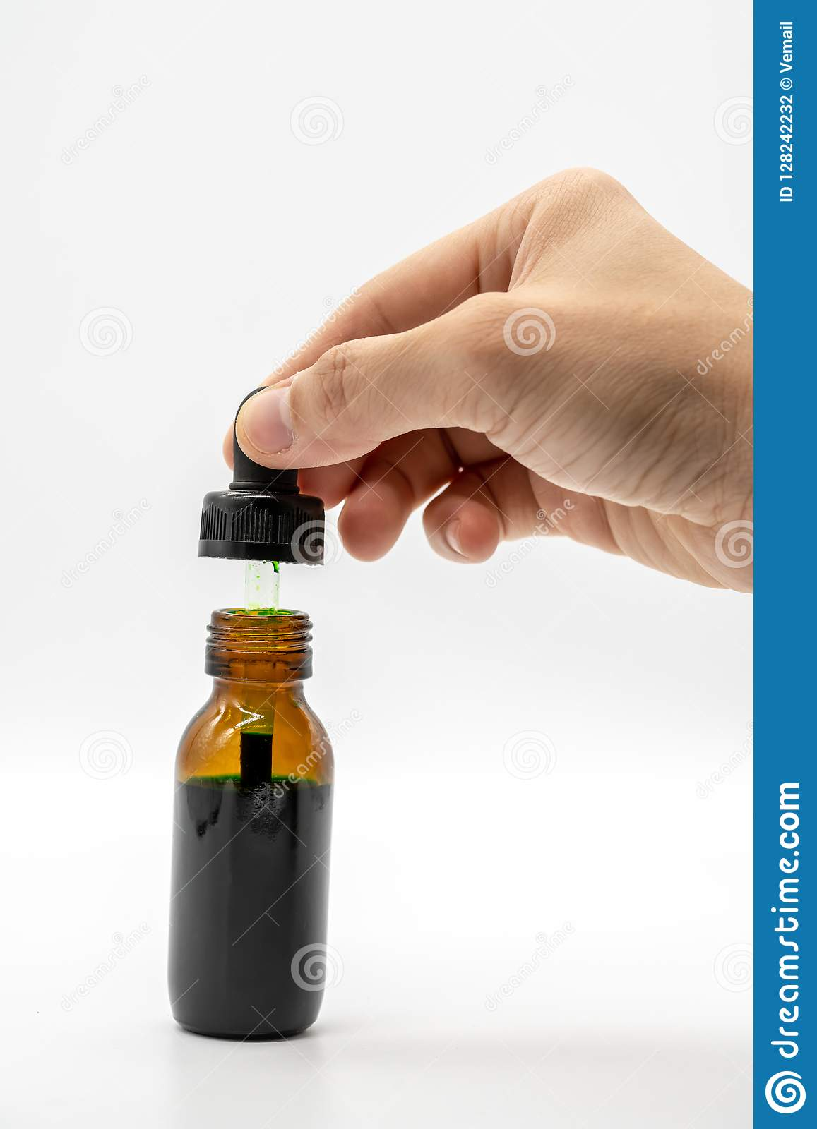 Hand holding the dropper with red color over the amber glass bo