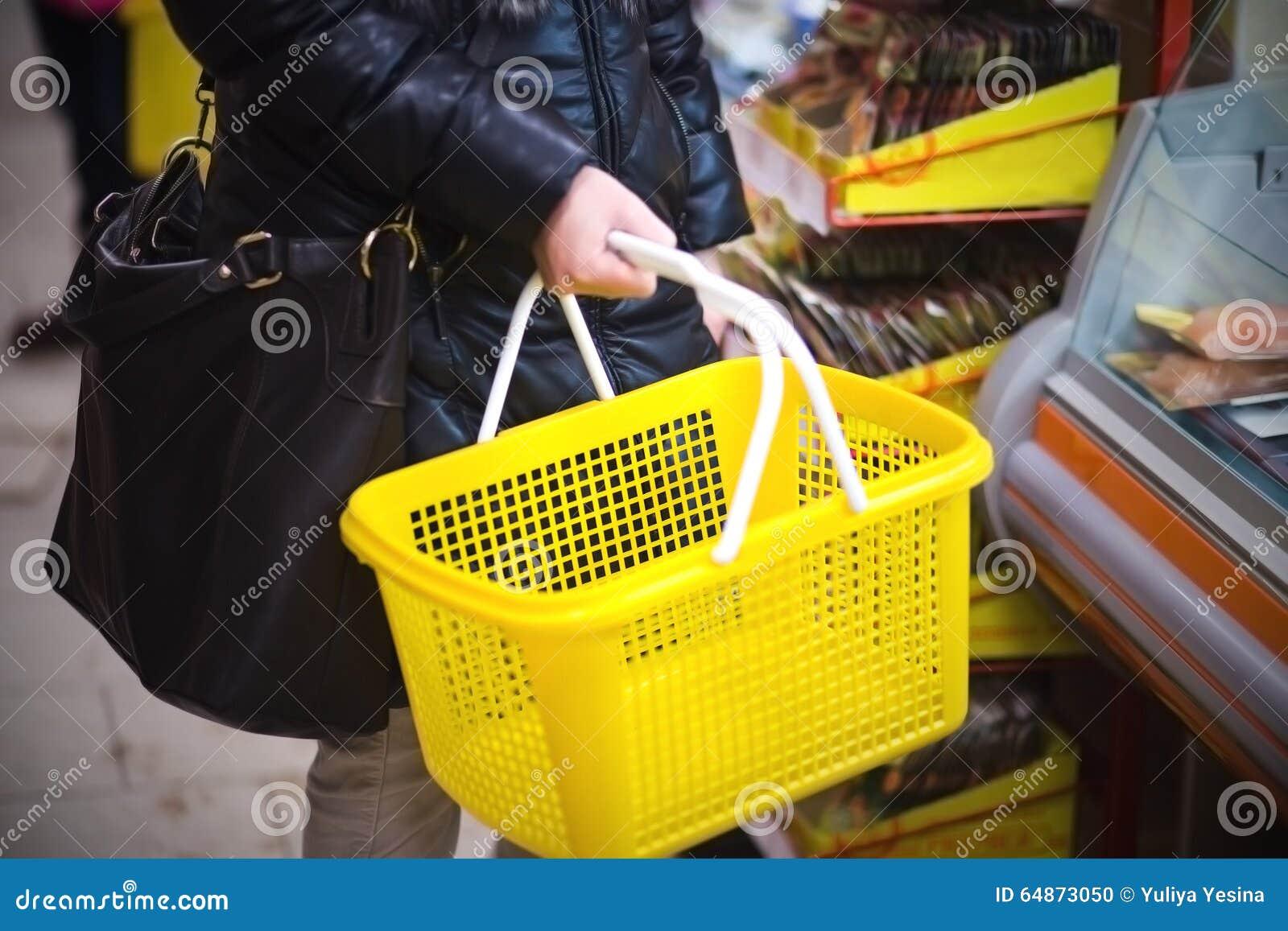 Hand holding empty shopping basket