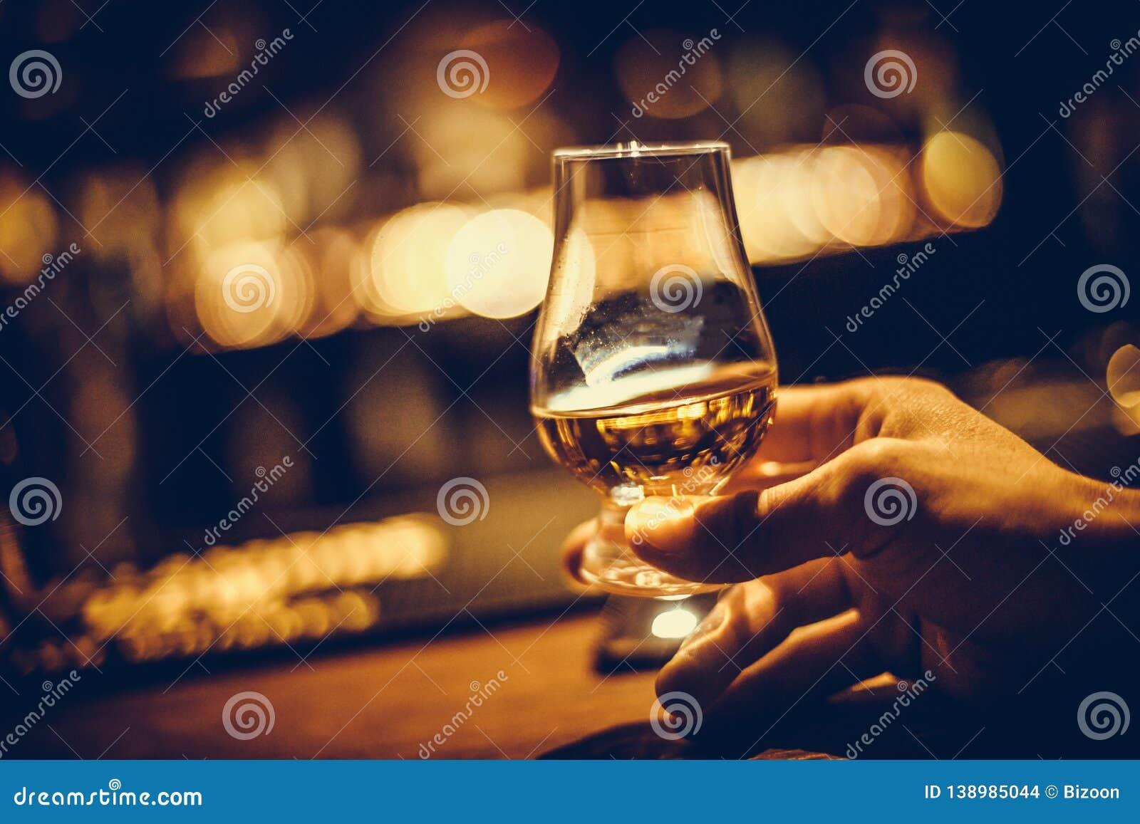 Hand holding a Glencairn single malt whisky glass