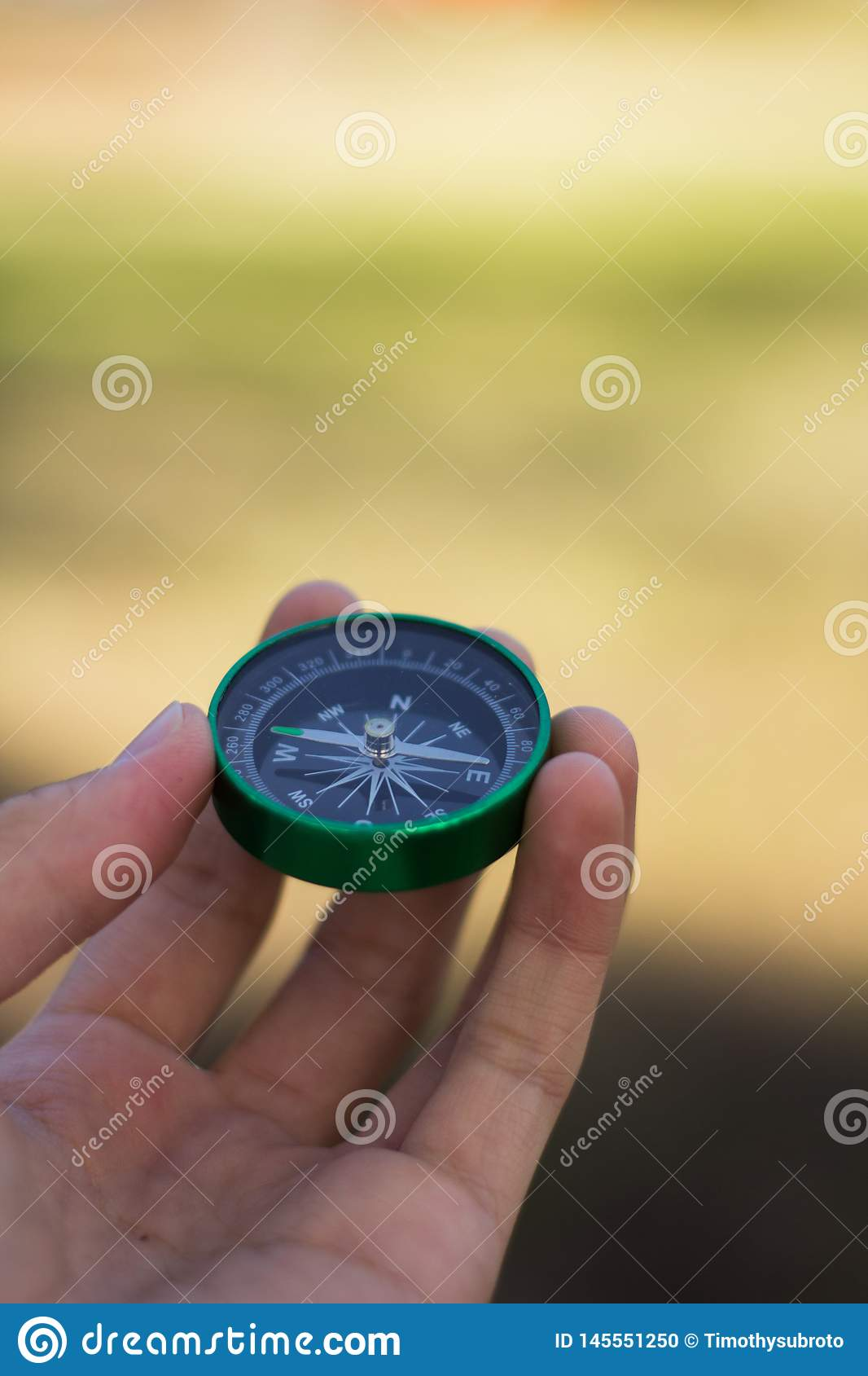 Hand Holding Green Compass Pointing West