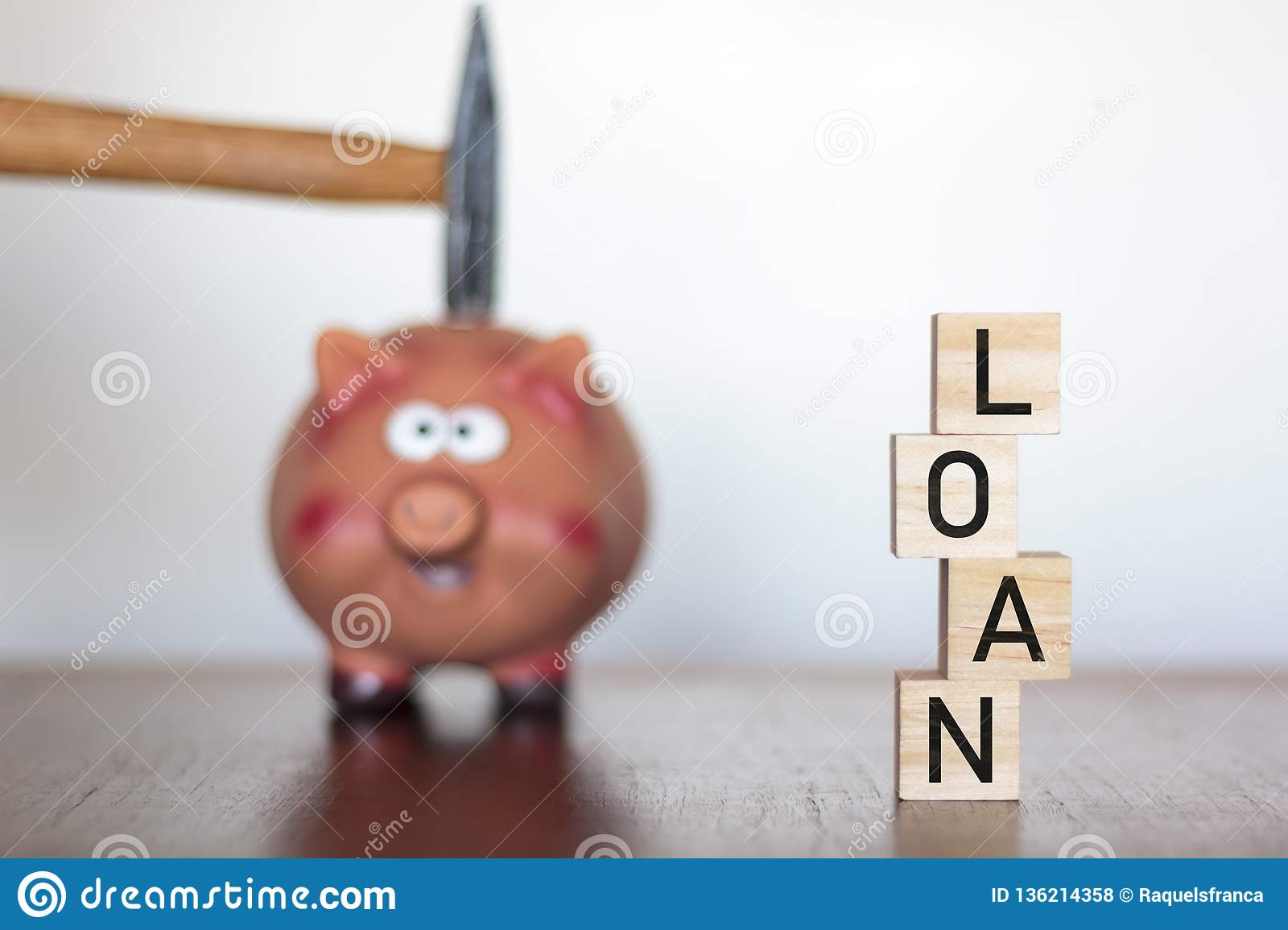 Hand holding a hammer above a Piggy bank and the word LOAN written on wooden cubes
