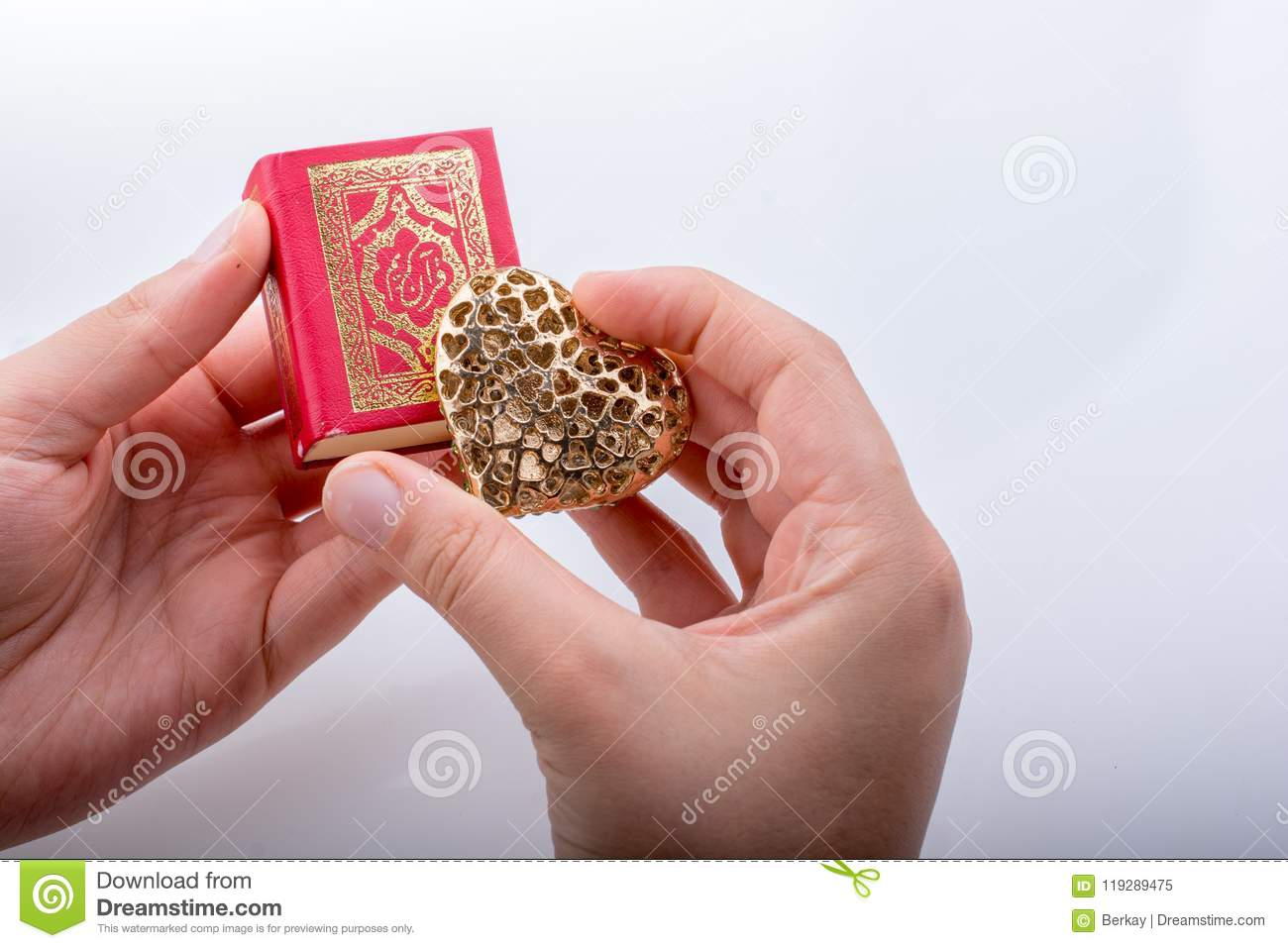 Hand Holding Heart Shape And Islamic Holy Quran Stock Image