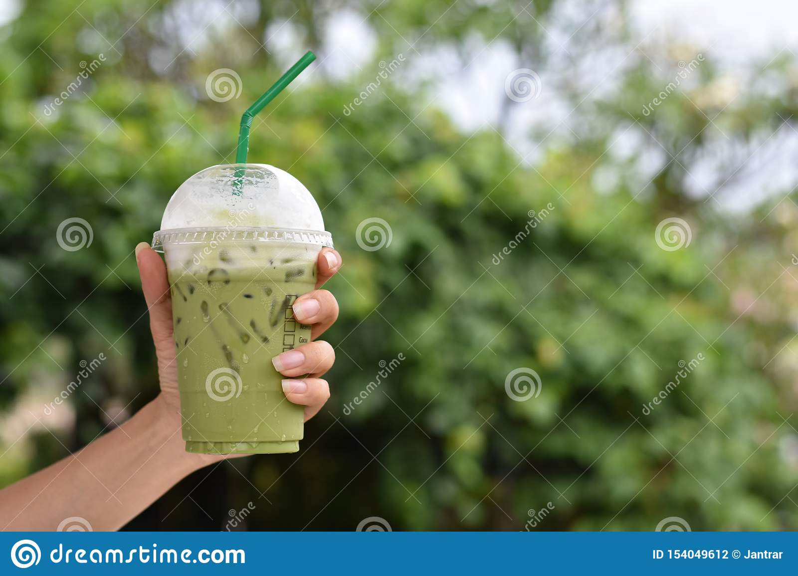 Hand holding of iced green tea in plastic glass.