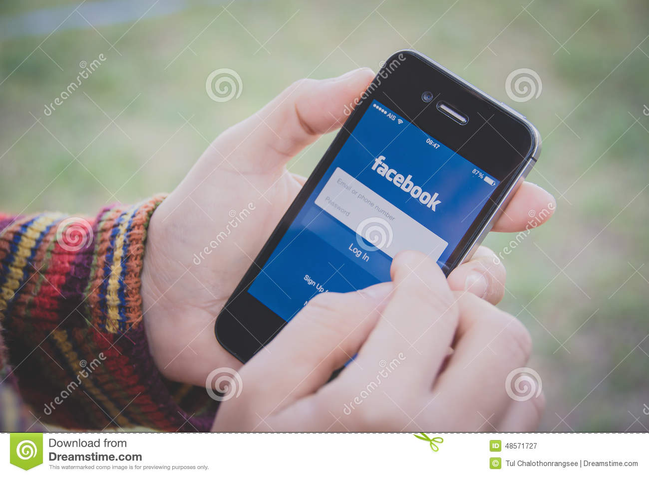 Hand holding Iphone and using Facebook application