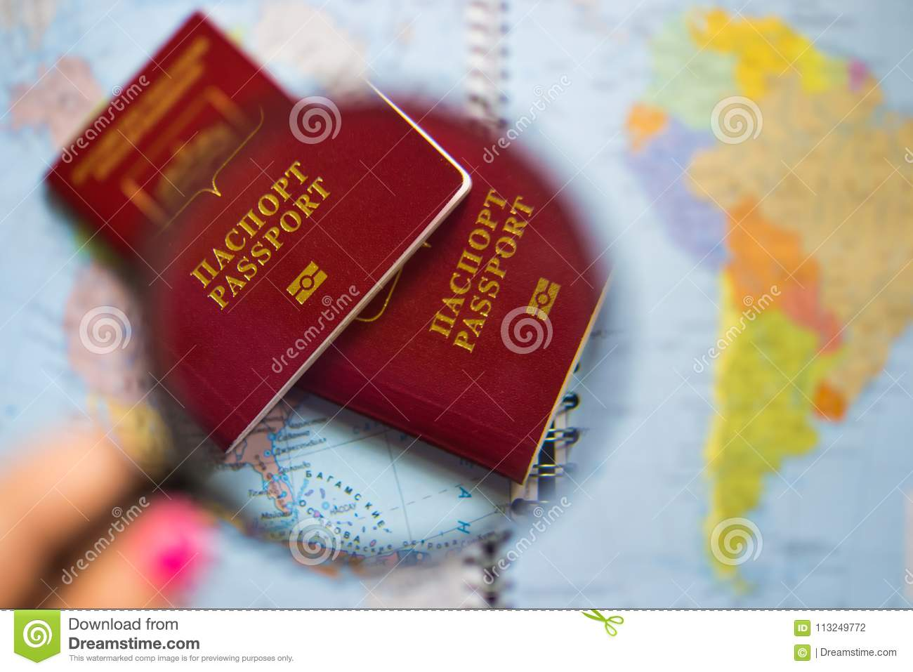 Passport under the glass of the magnifying glass on the background map of the world