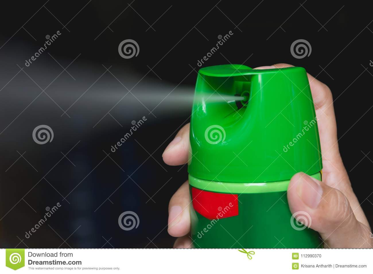 Hand holding mosquito spray. Human using mosquito spray from bot