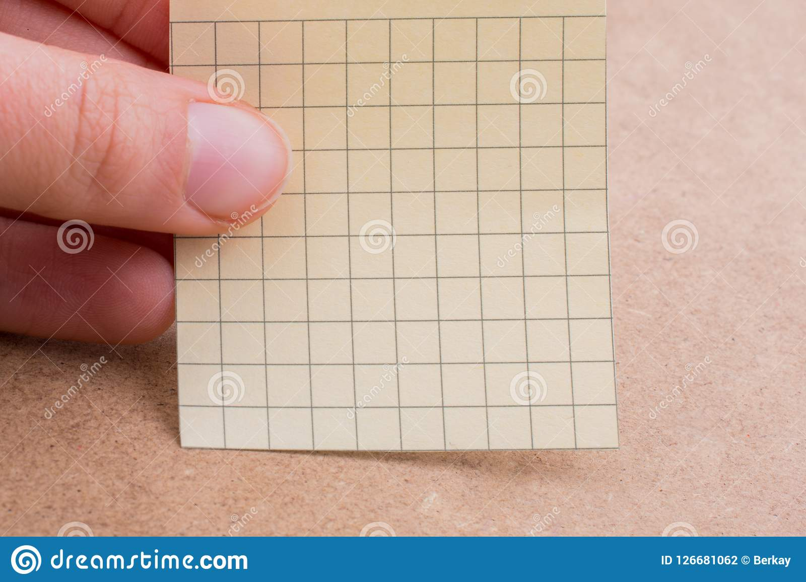 Hand holding a note paper in hand. Hand holding a note paper on a brown background Stock Photography