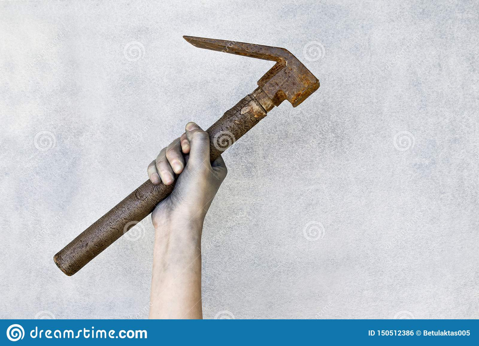 Hand holding old rusty hammer on gray background.