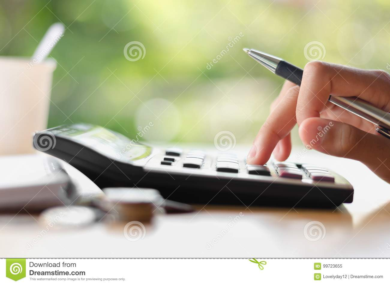 hand holding pen and pressing calculator button for business accounting of finance