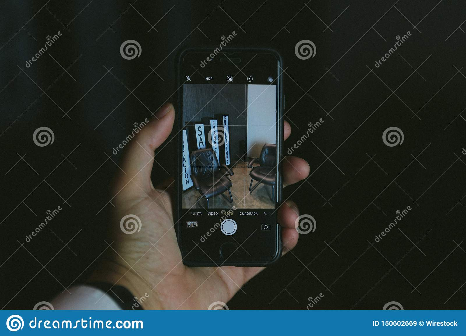 Hand holding a smart phone in a camera mode shooting some posters