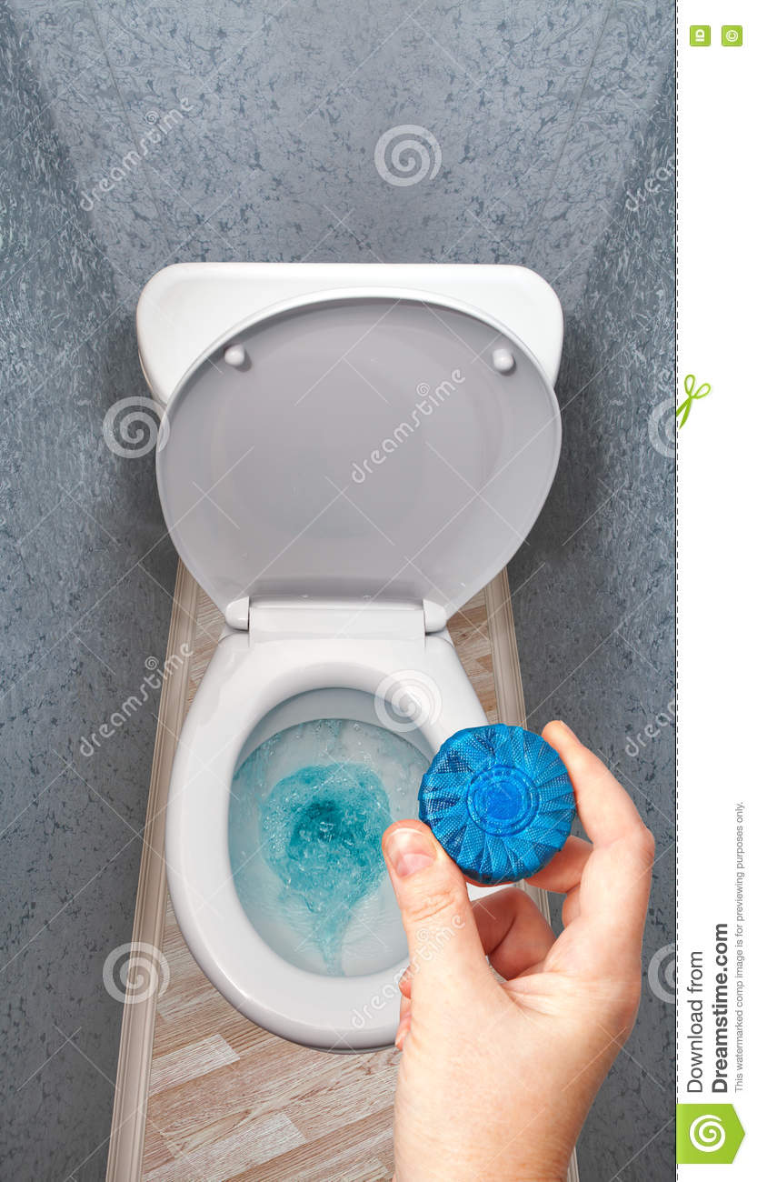 Hand Holding Solid Detergent Is Put In Toilet Bowl Tank