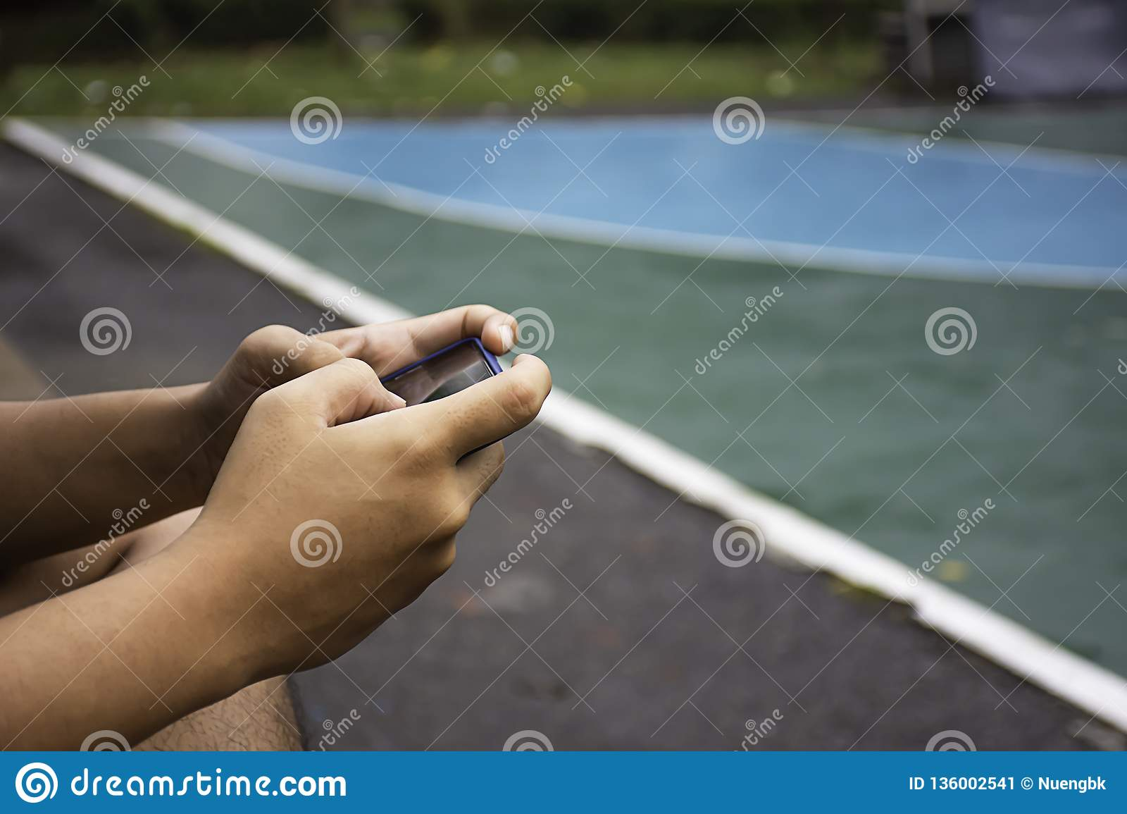 Hand holding telephone Background on basketball court
