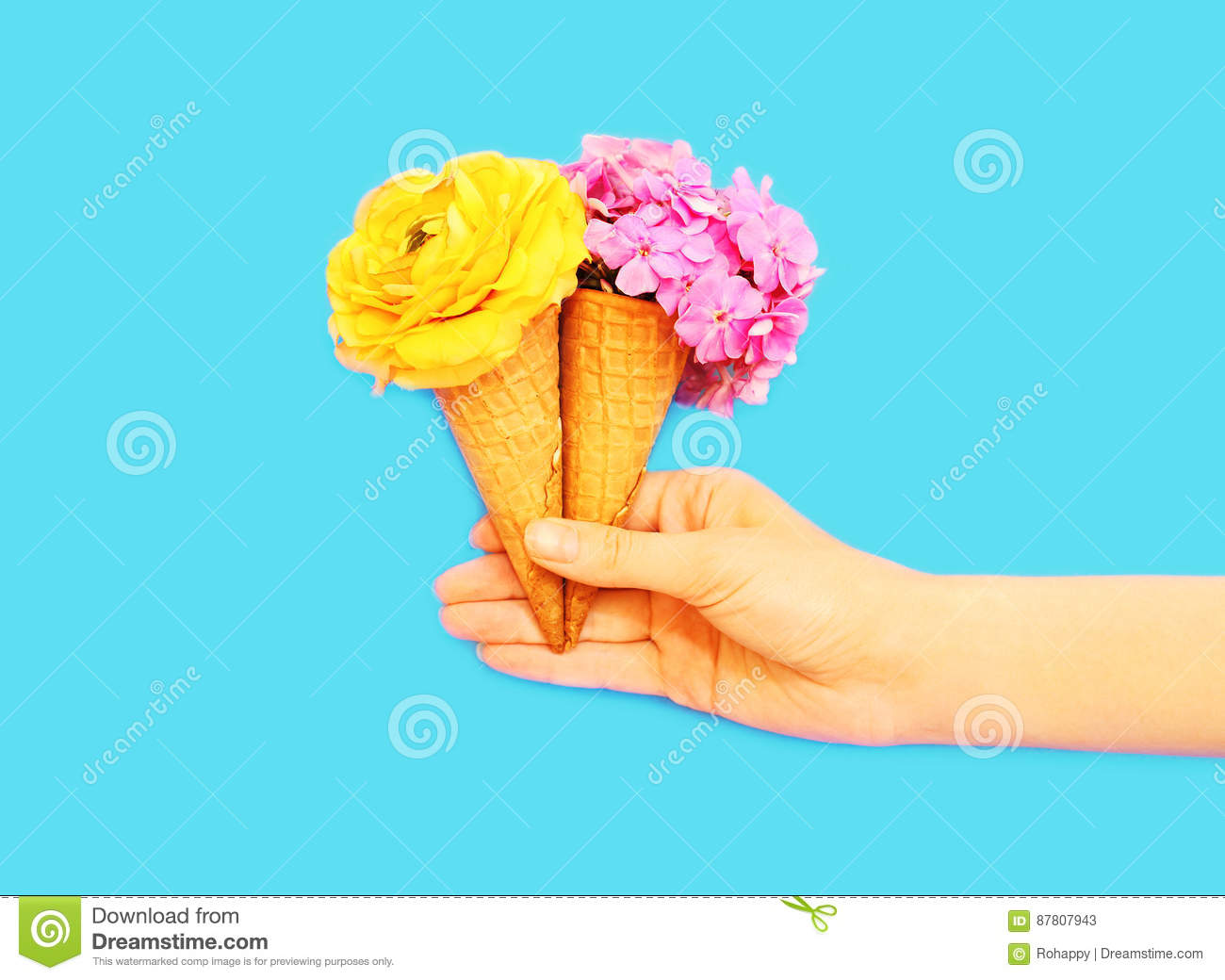 Hand holding two ice cream cone with flowers over blue