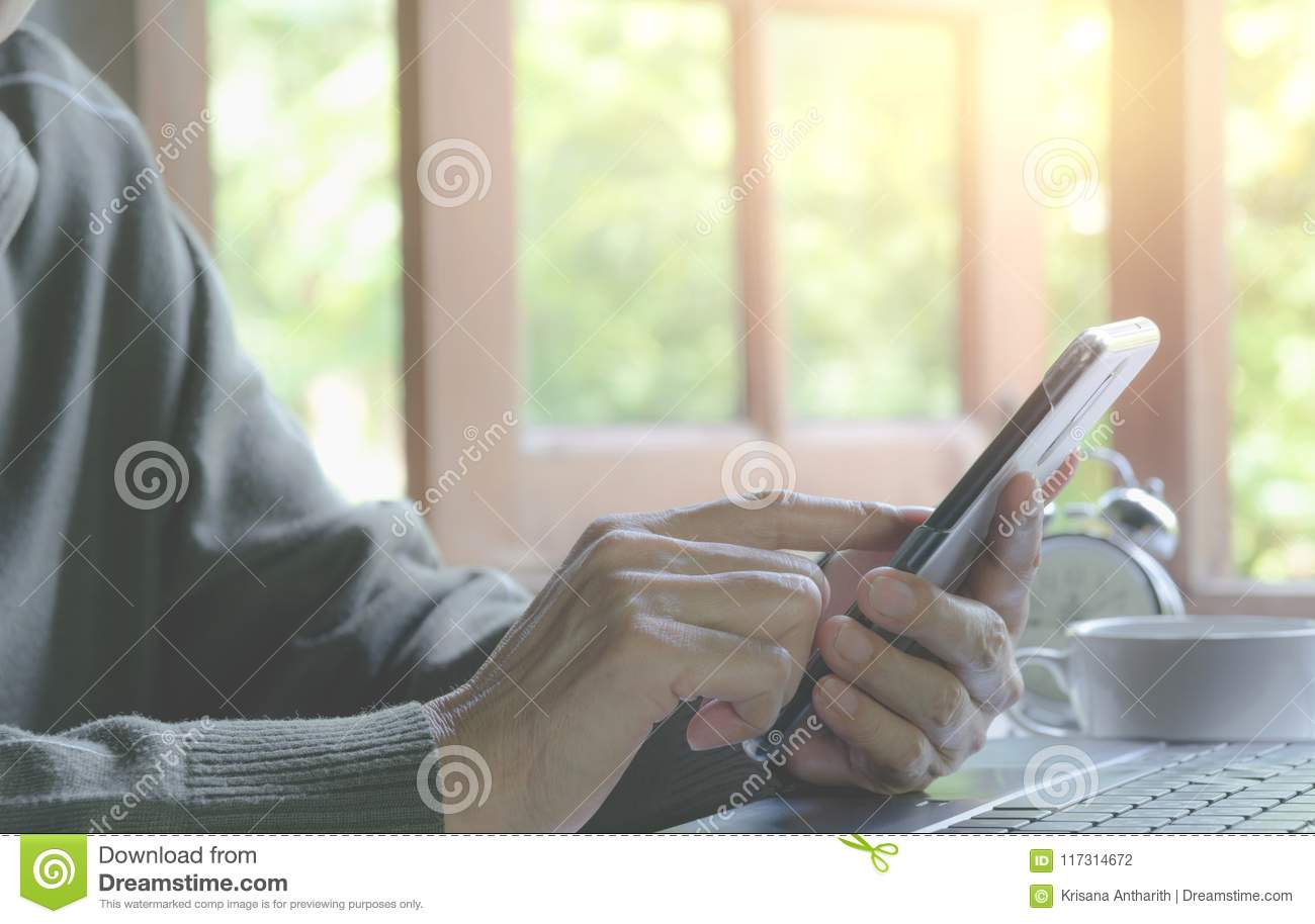 Hand holding and using a smart phone. Technology and communication concept.