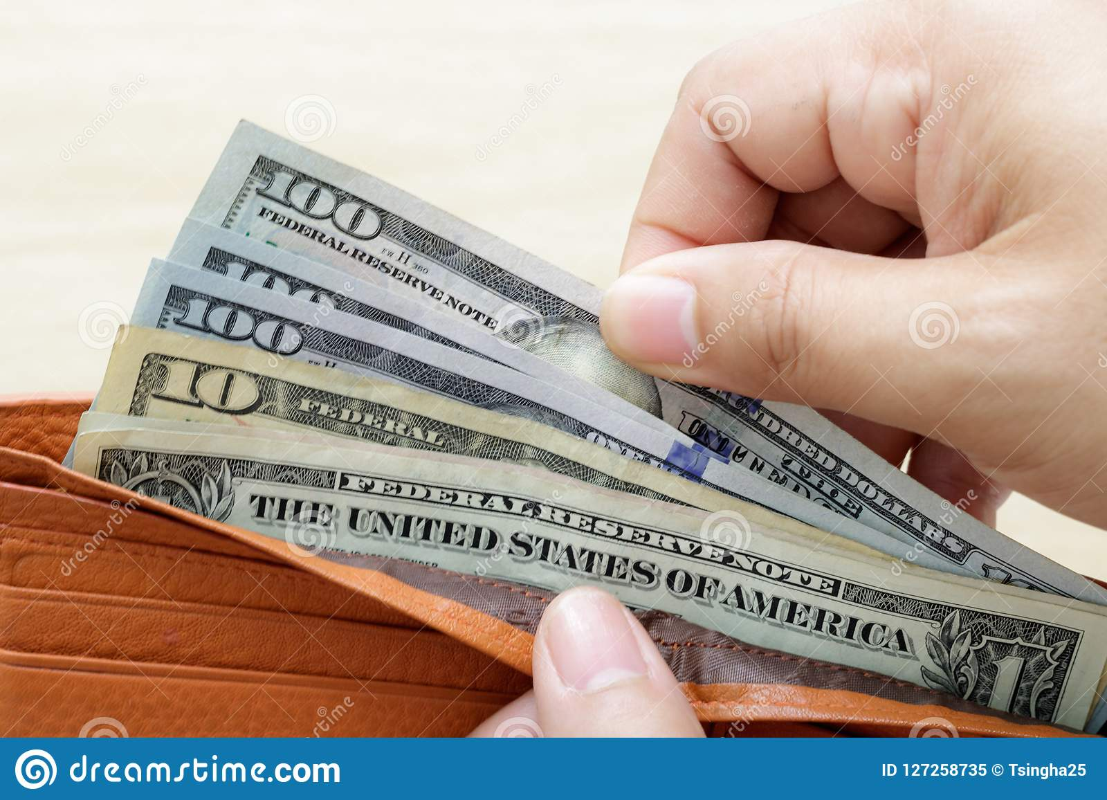 Hand holding wallet with US Dollar banknote and taking out money