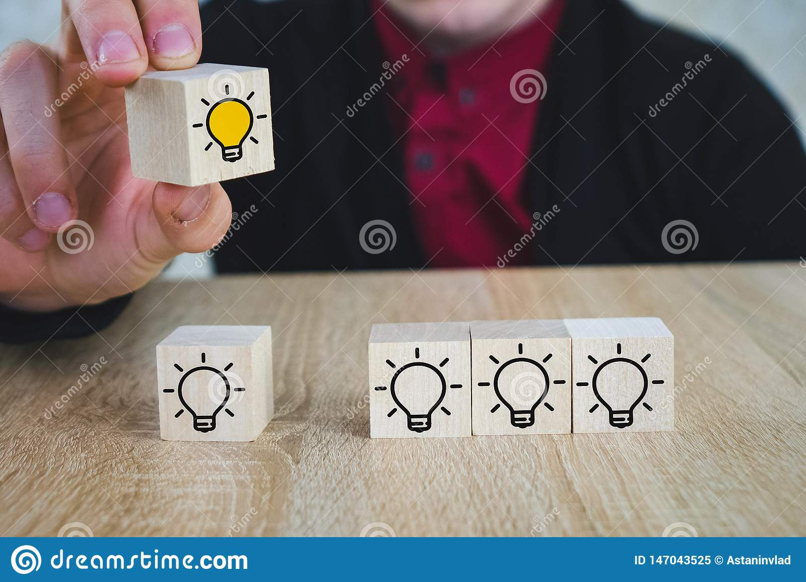 a hand holds a cube with a burning lamp when all the other lamps are extinguished, which symbolizes the New Idea, the concepts of