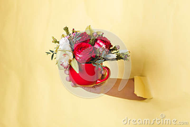Hand Holds Small Vase With Flowers And Rose Breakes Through A Yellow