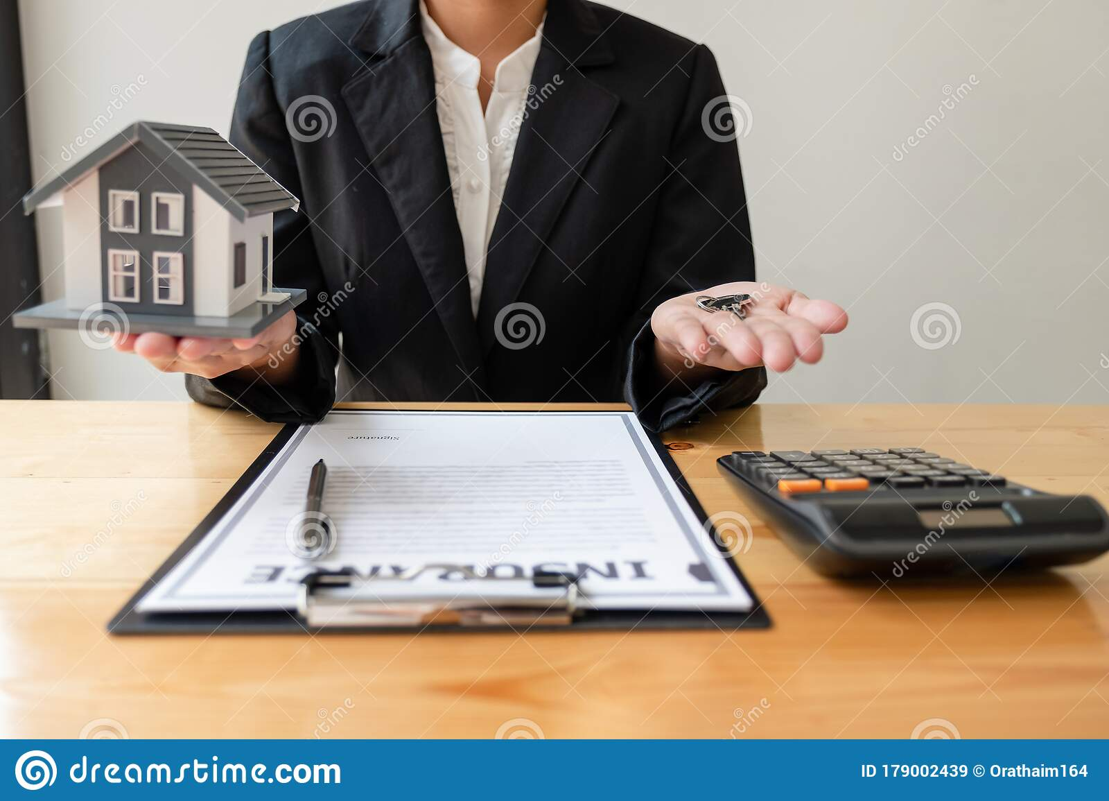 The Hand Of A Home Insurance Agent Is Holding A Modelhome ...