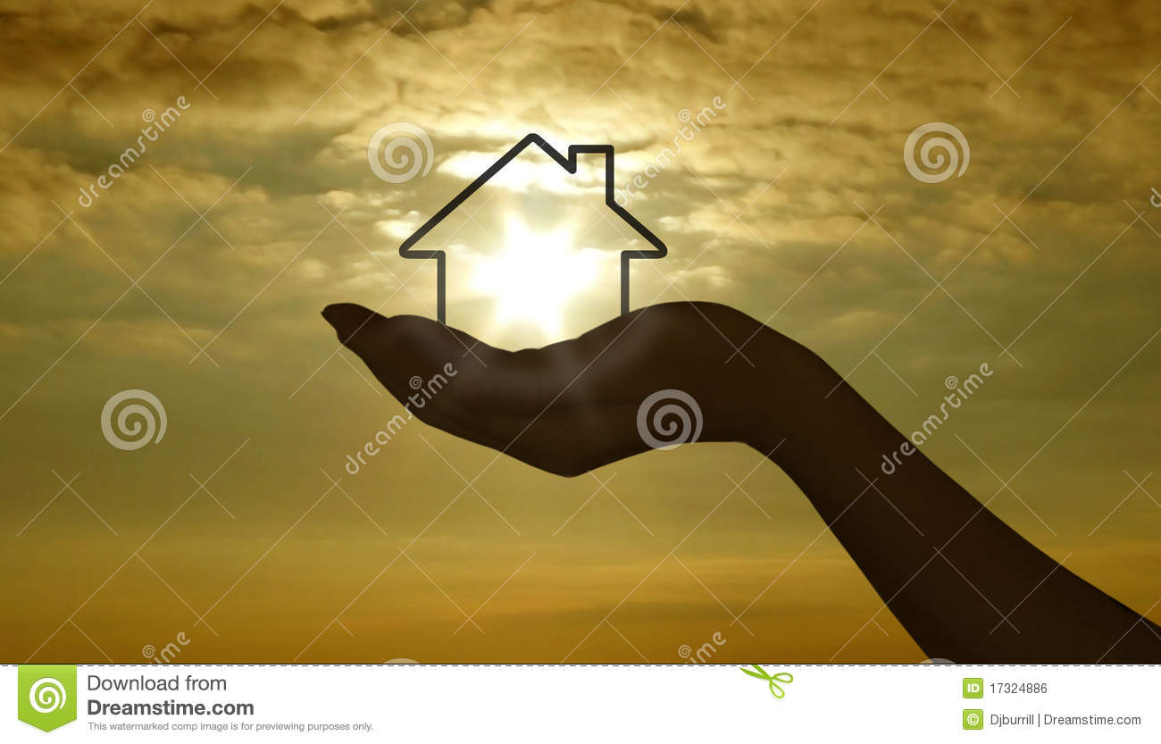 Hand with house at sunset