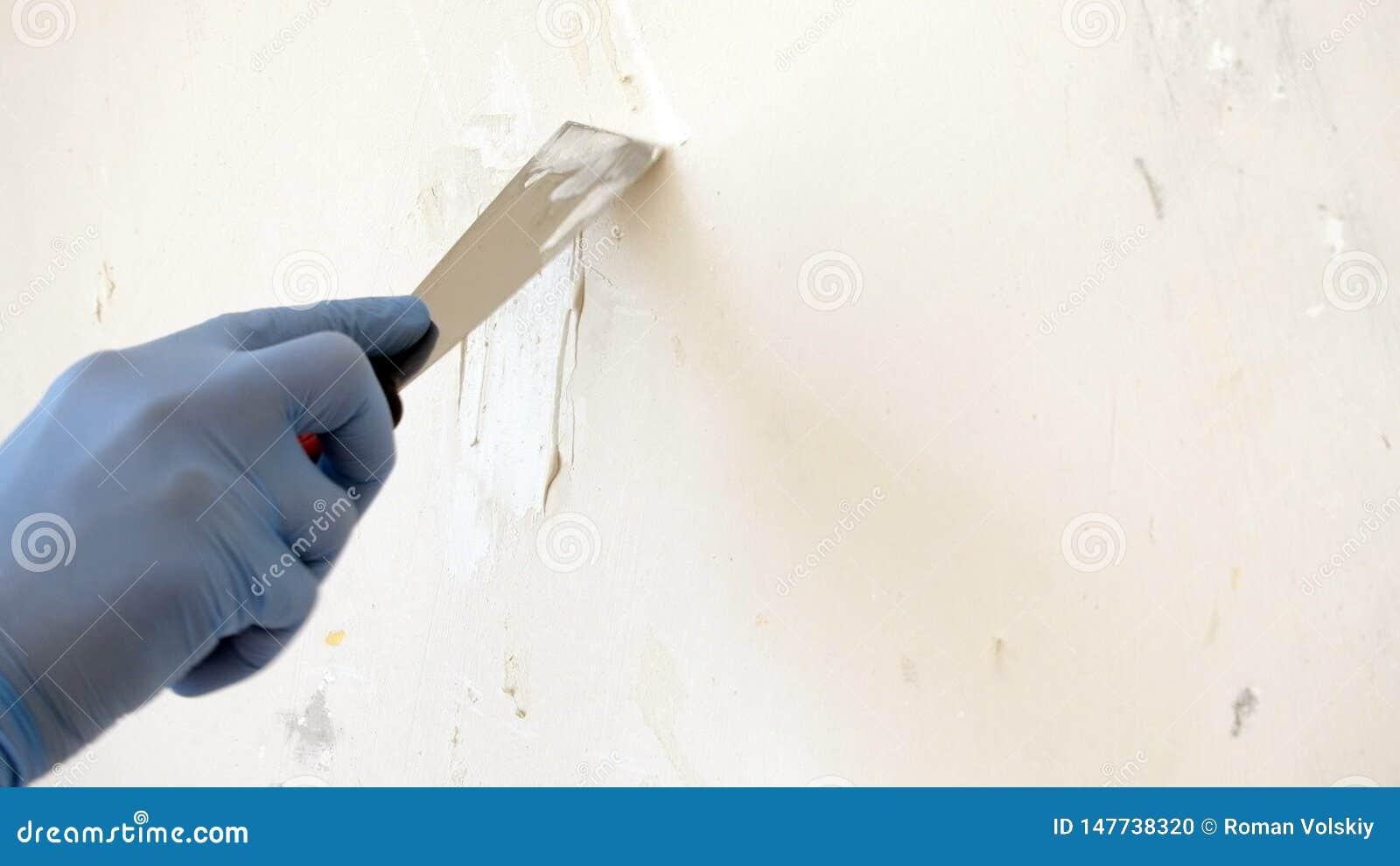 Hand i blå handske med spackelreparationsväggen, processen av att applicera ett lager av spackel, avslutande arbete för reparatio