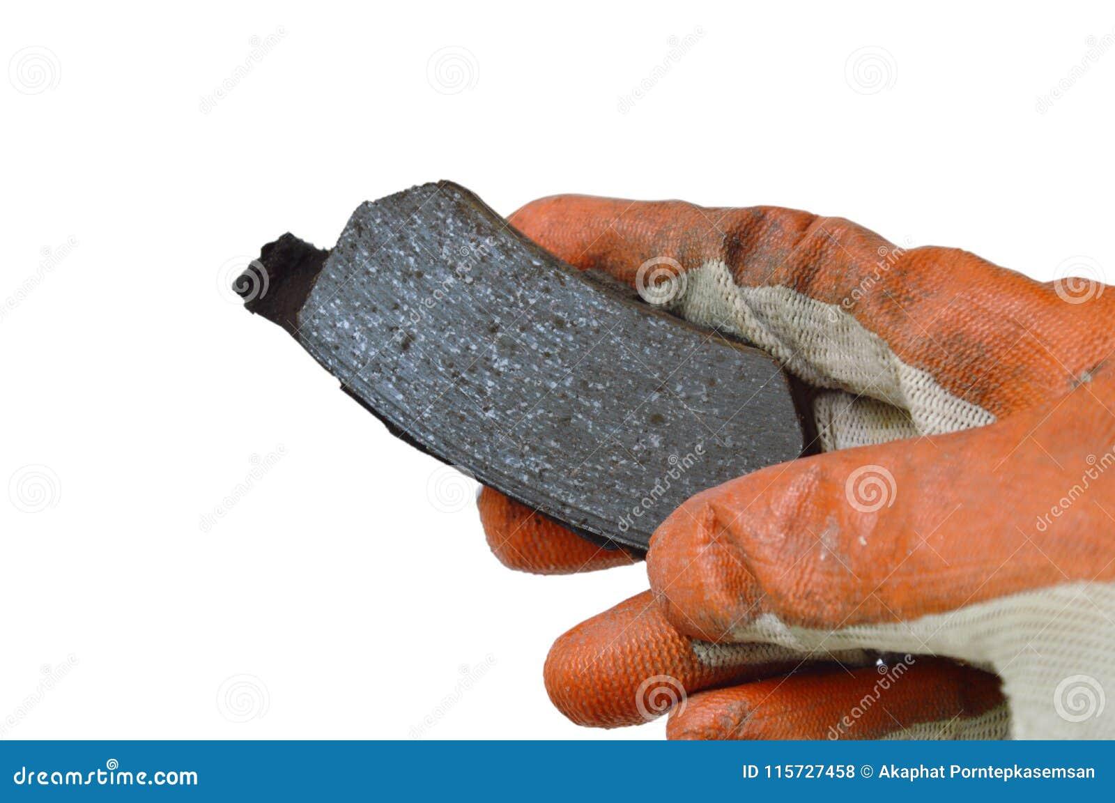 Hand i handsken som rymmer ogiltigt bromsfoder för ändrande på vit bakgrund