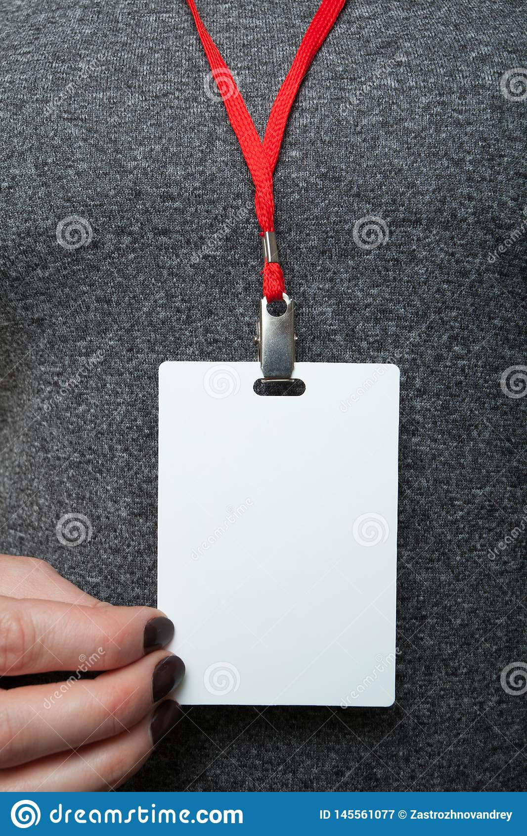 Hand with identification of a white blank plastic identity card with a red rope on a background of gray clothes. Mock up