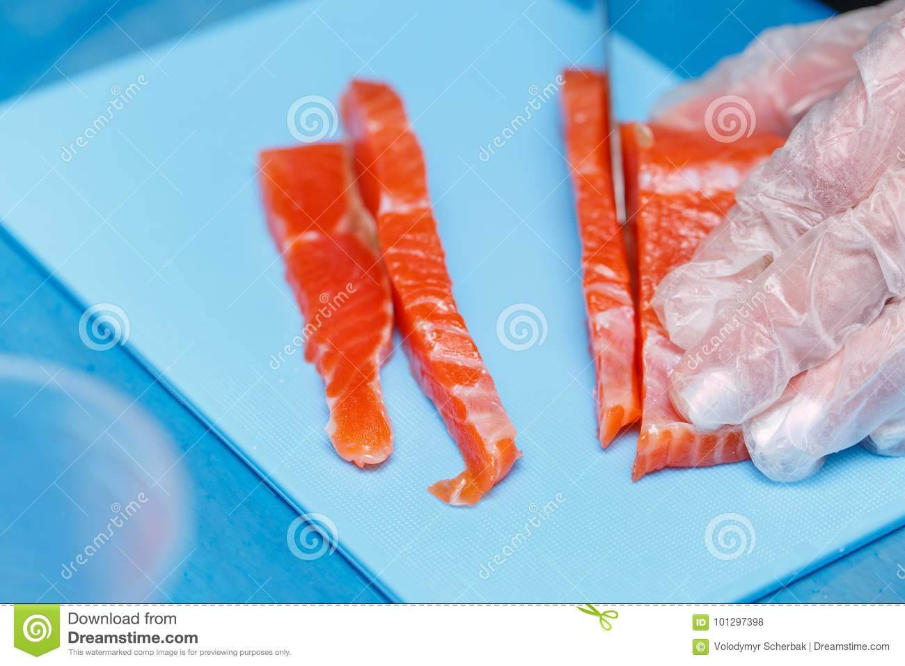 Hand With Knife Cuts Fish Raw Fish On Cooking Board Salmon Meat