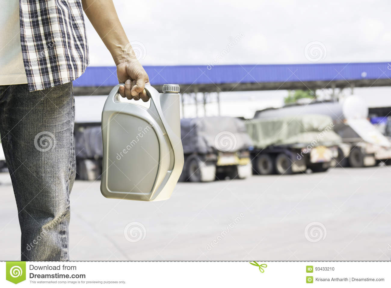 Hand of male holing gray plastic canister of motor oil on gas st