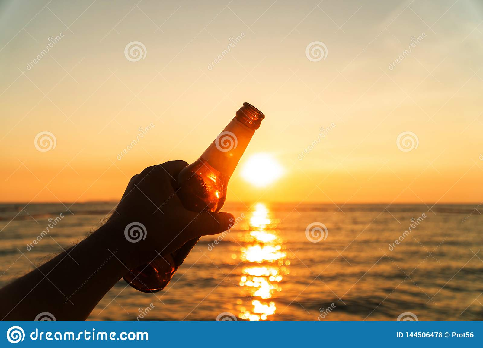 Hand of man is holding beer bottle and holds his hand up on the sky in evening with sunset. celebrating on holiday at the beach in