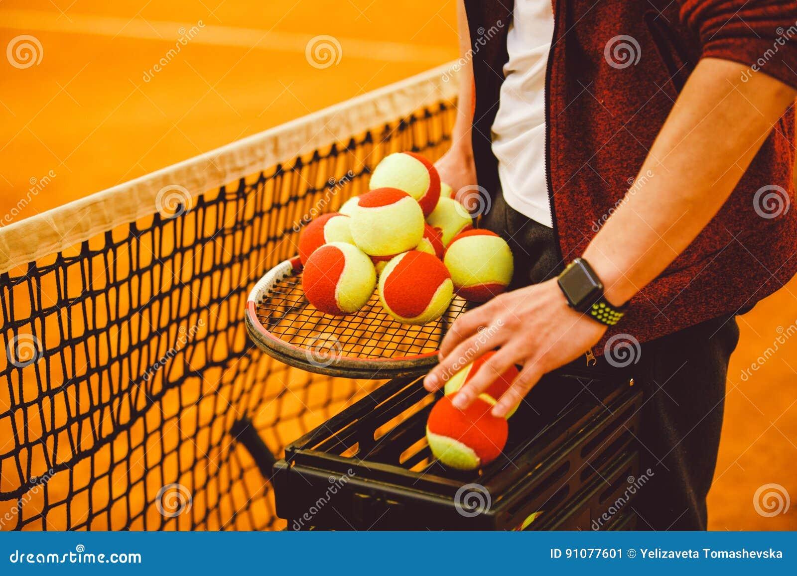 Hand man holding a tennis racket and a lot of goals. Basket for tennis balls,