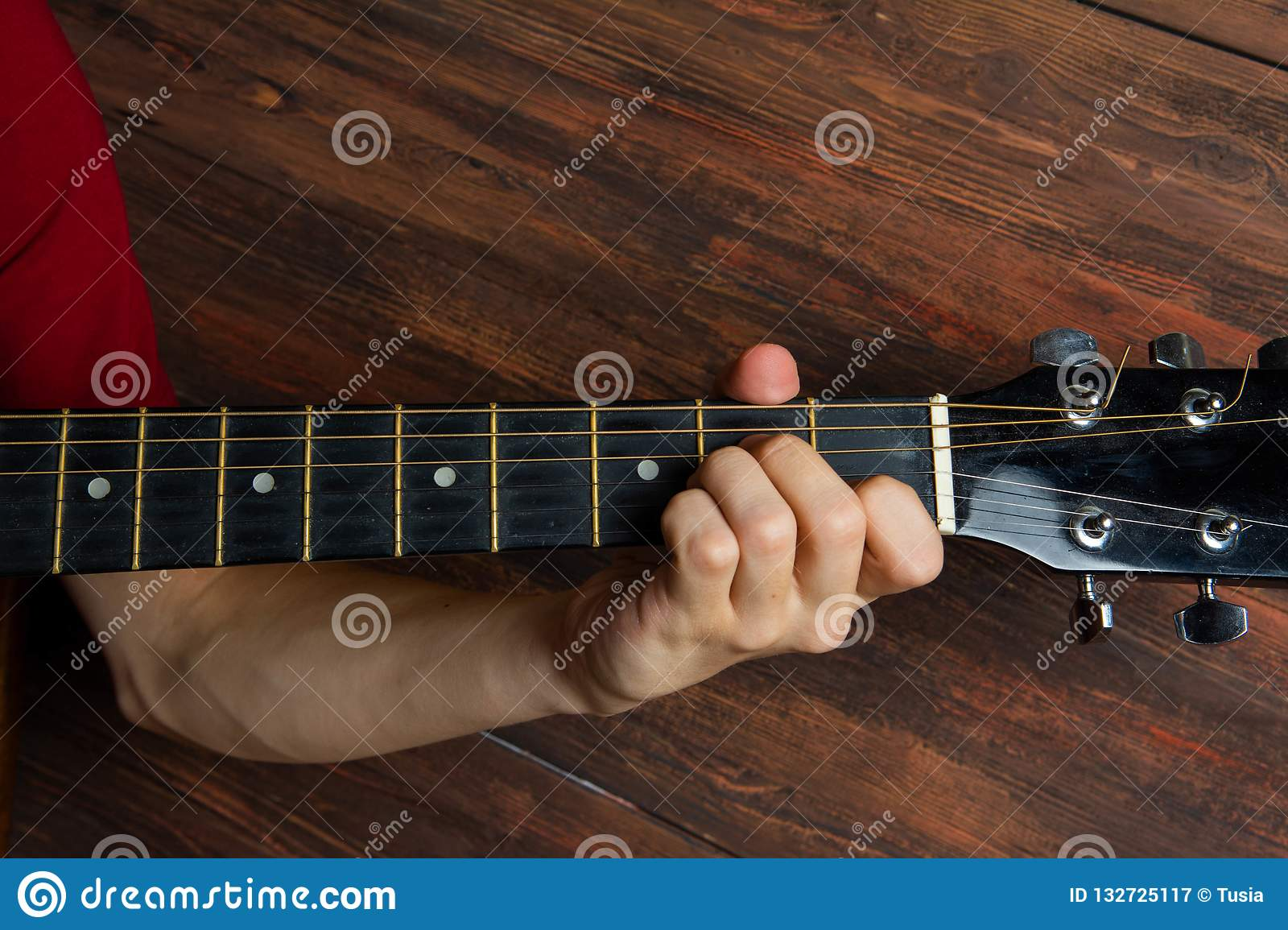 Hand of man playing six-string guitar on wooden background. Template for concert poster