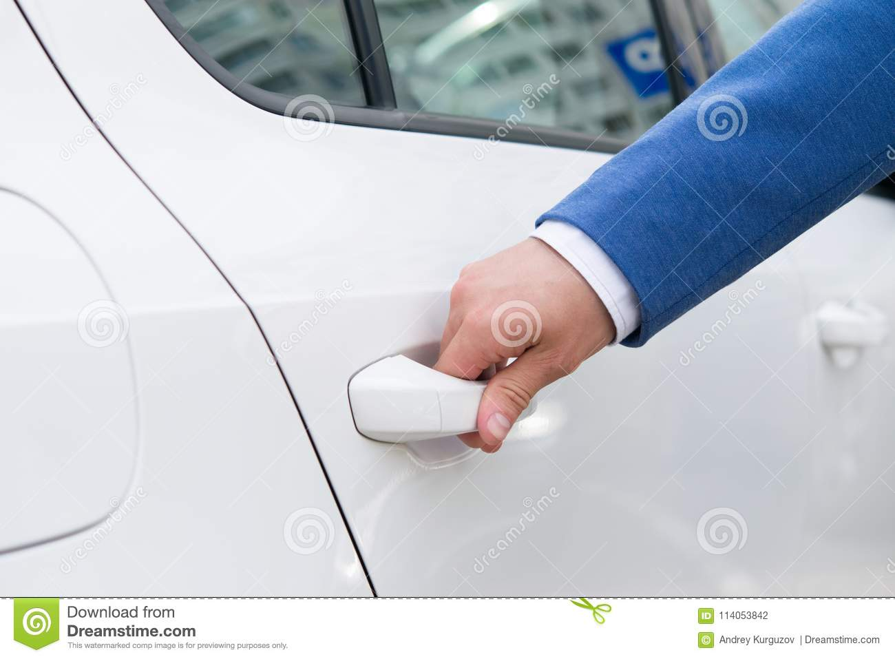 Hand of a man trying to open the back door of a white car