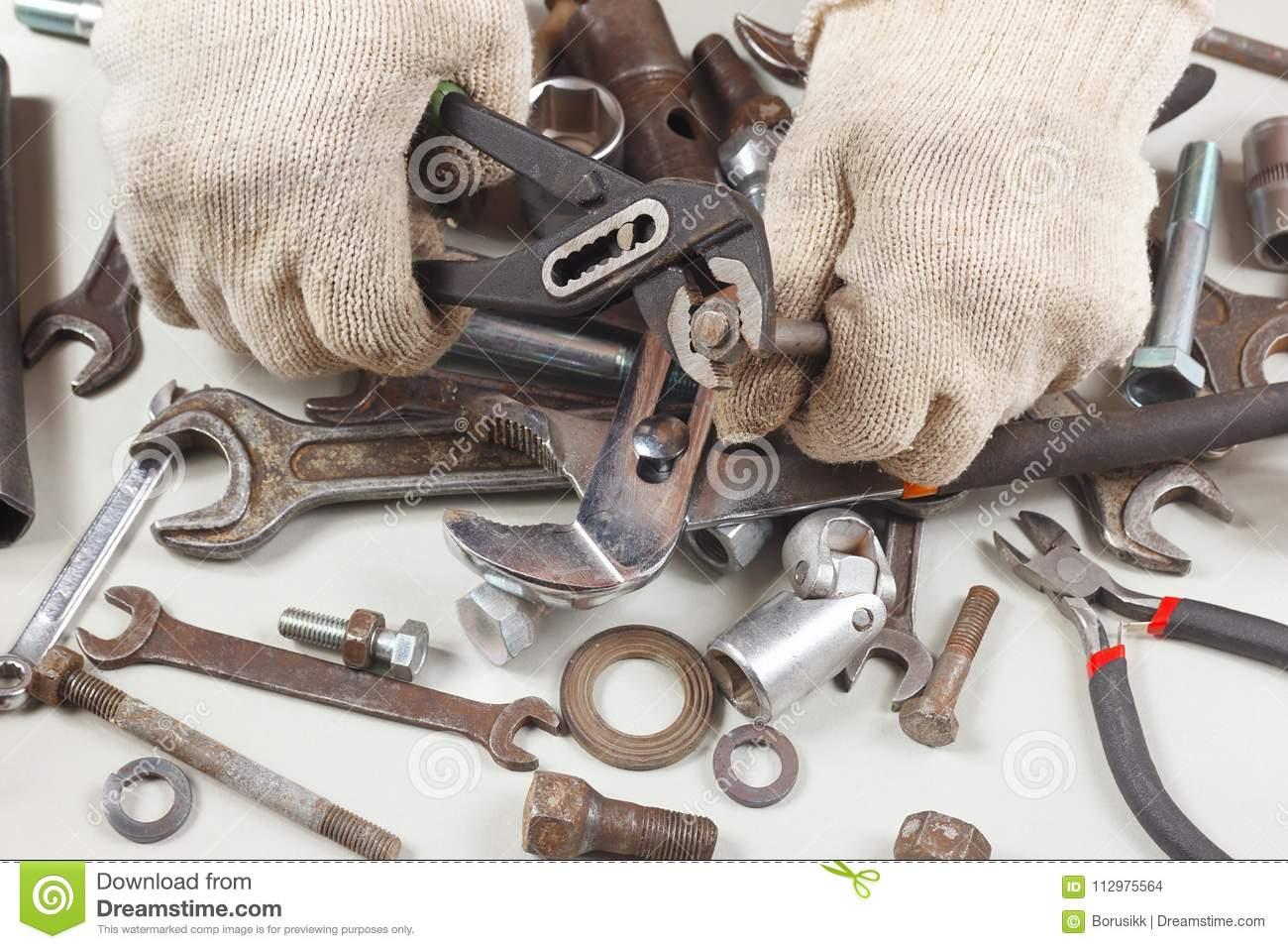Hand of master in gloves with wrench to tighten the nut