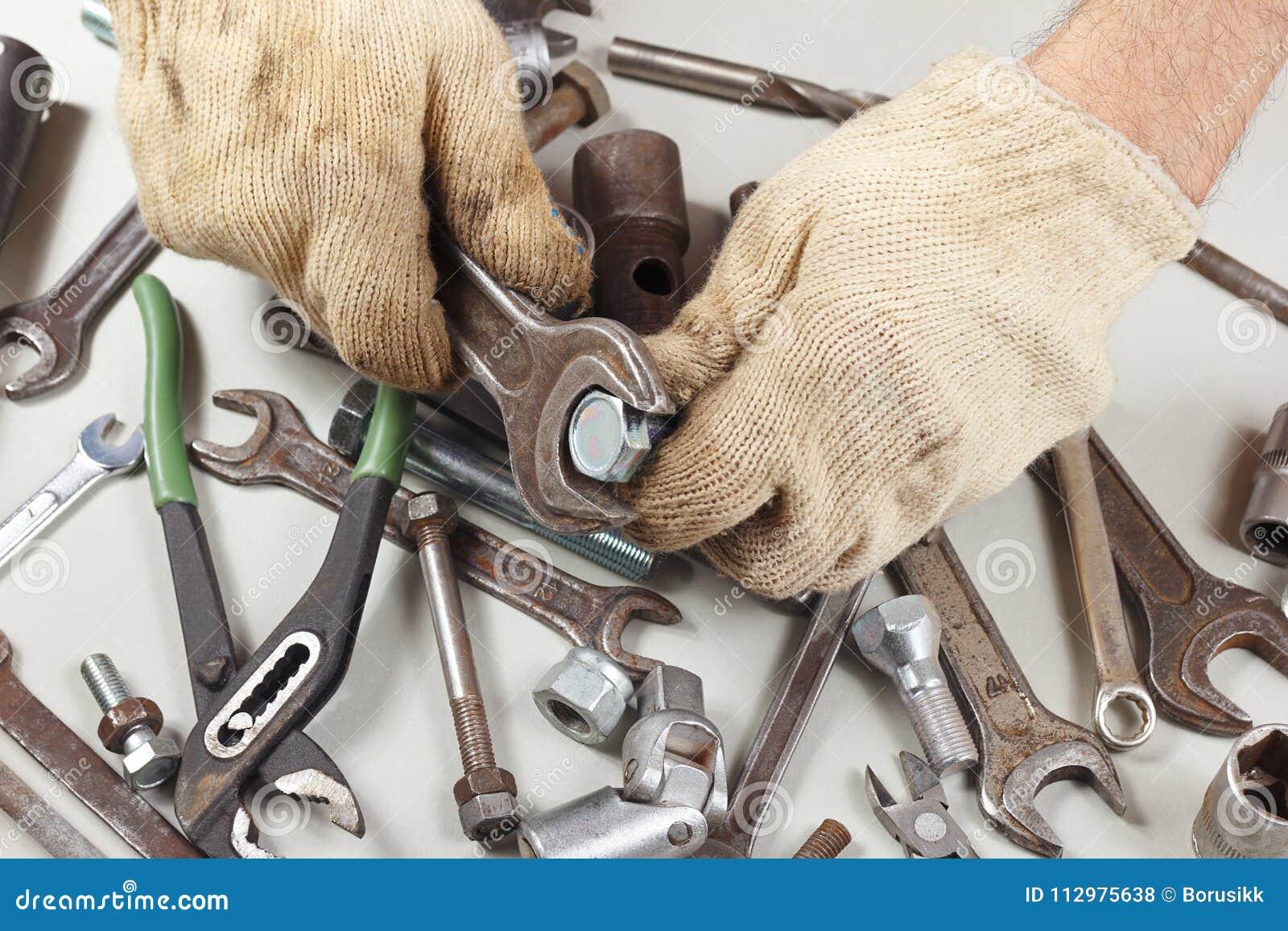 Hand of mechanic in gloves repairing parts of the mechanism in workshop
