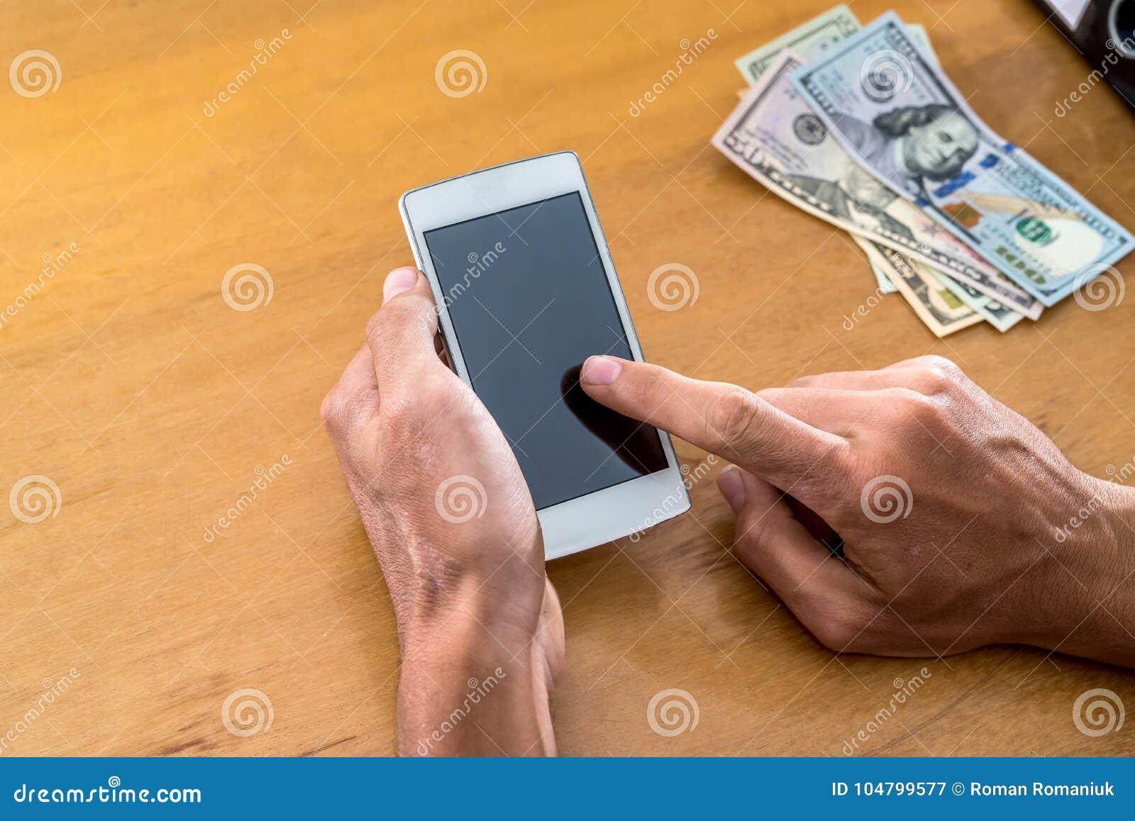 Hand med telefonen och dollar