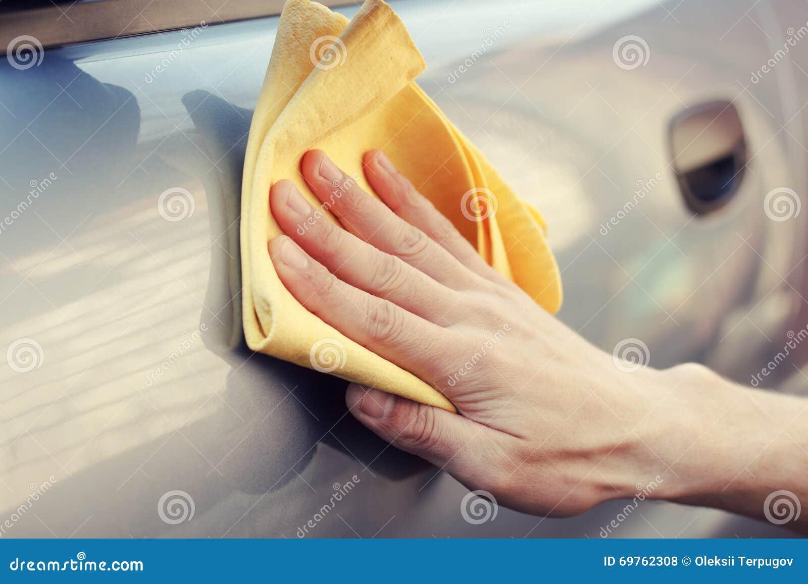 Hand med trasapolermedel bilen