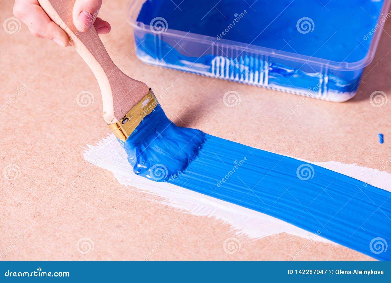Hand met borstelverven met blauwe verf